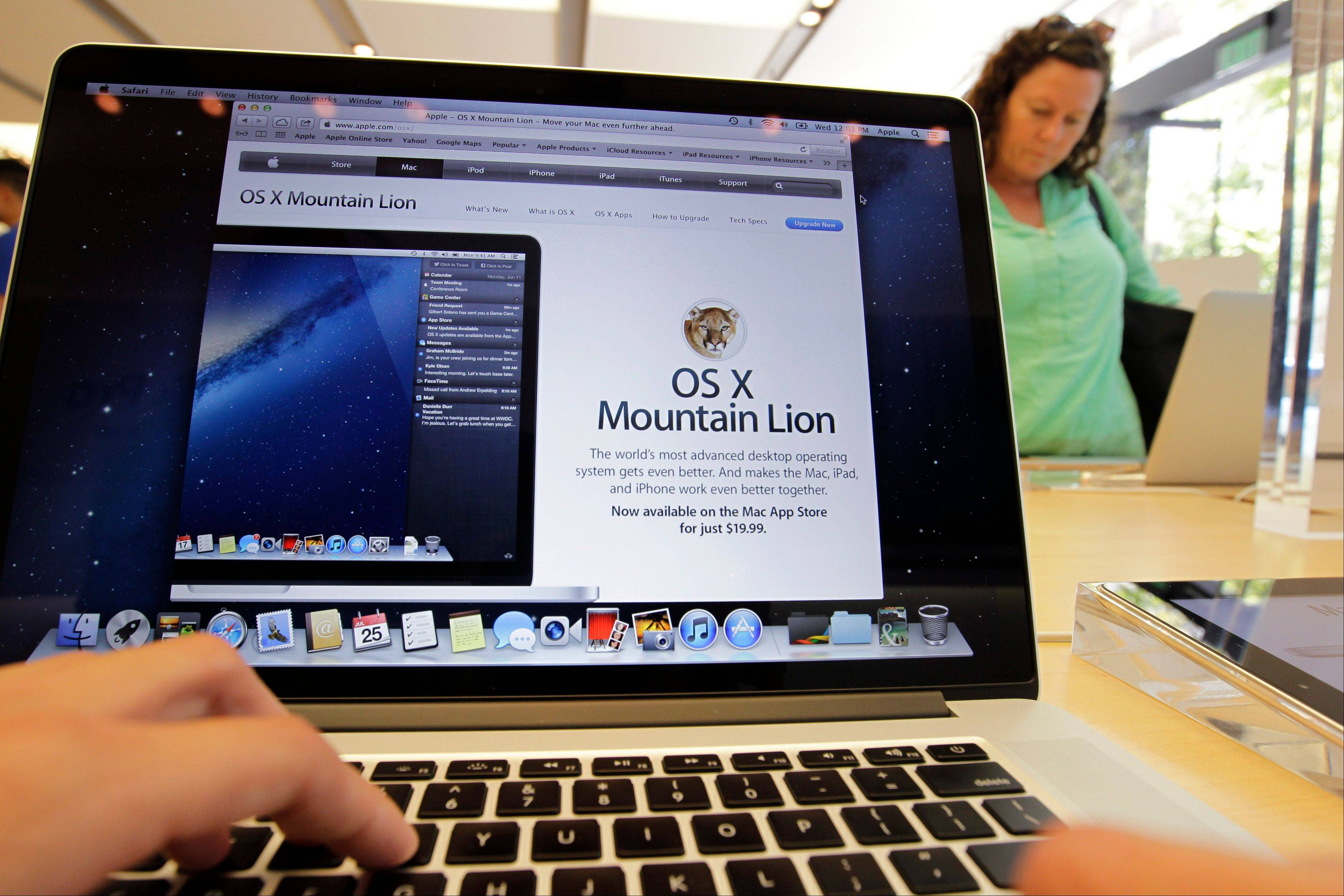 A customer looks at the new OS X Mountain Lion operating system at an Apple store in Palo Alto, Calif. Apple Inc. released its new operating system for Mac computers on Wednesday, with features borrowed from mobile devices and a tighter integration with online file storage.