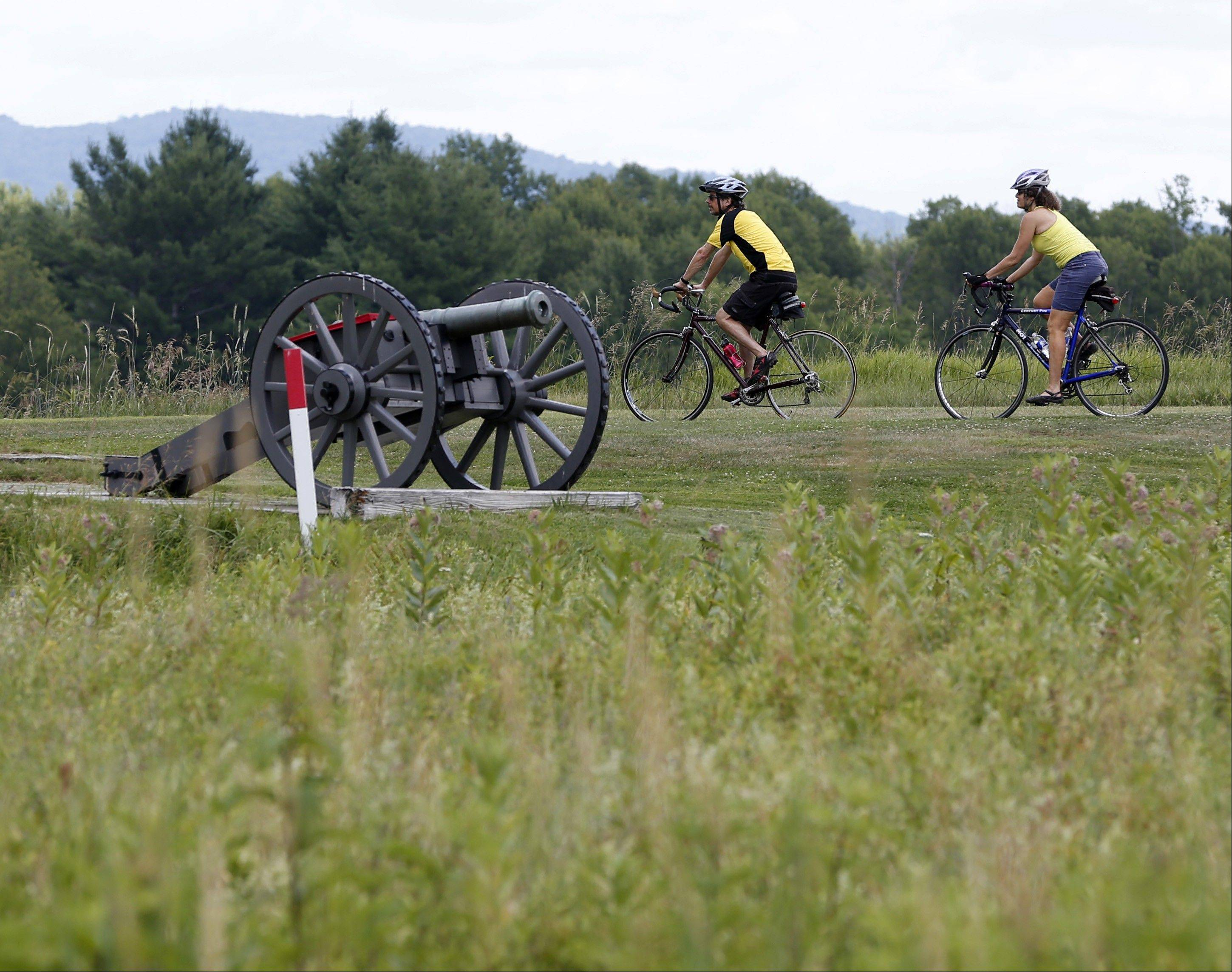 Eric Epstein, left, and Isabelle Davidowitz, of Braddock Heights, Md., ride past a cannon on a bike tour of Saratoga National Historical Park.