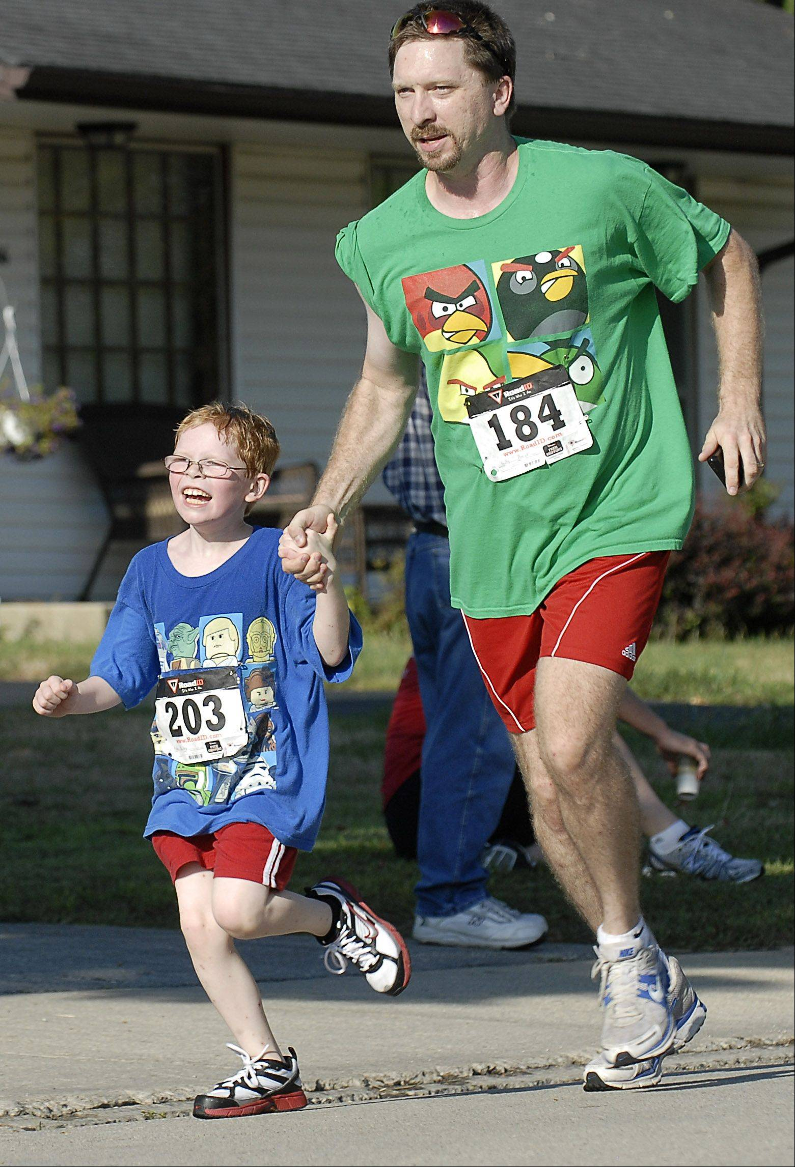 Aiden Bailey, 7, and his father, Patrick, both of Sugar Grove, join hands to cross the finish line together in the Sugar Grove Corn Boil 5K Run/Walk on Saturday. This was Aiden�s first race.