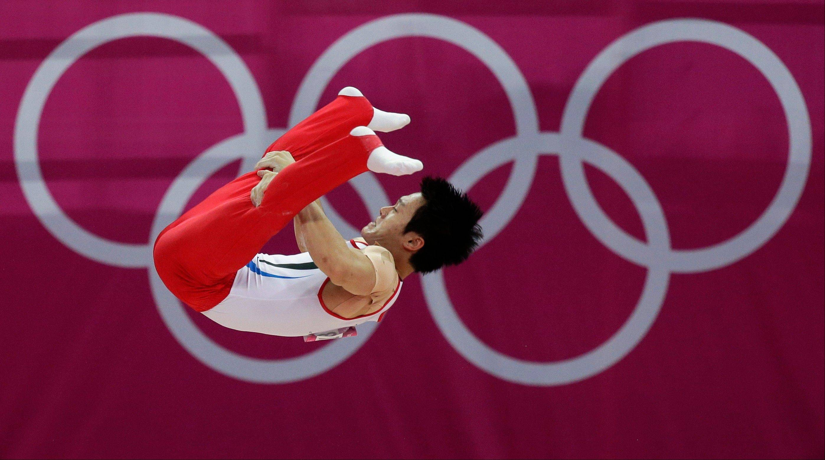 South Korean gymnast Kim Seungil performs on the parallel bars during the Artistic Gymnastic men�s qualification at the 2012 Summer Olympics, Saturday, July 28, 2012, in London.