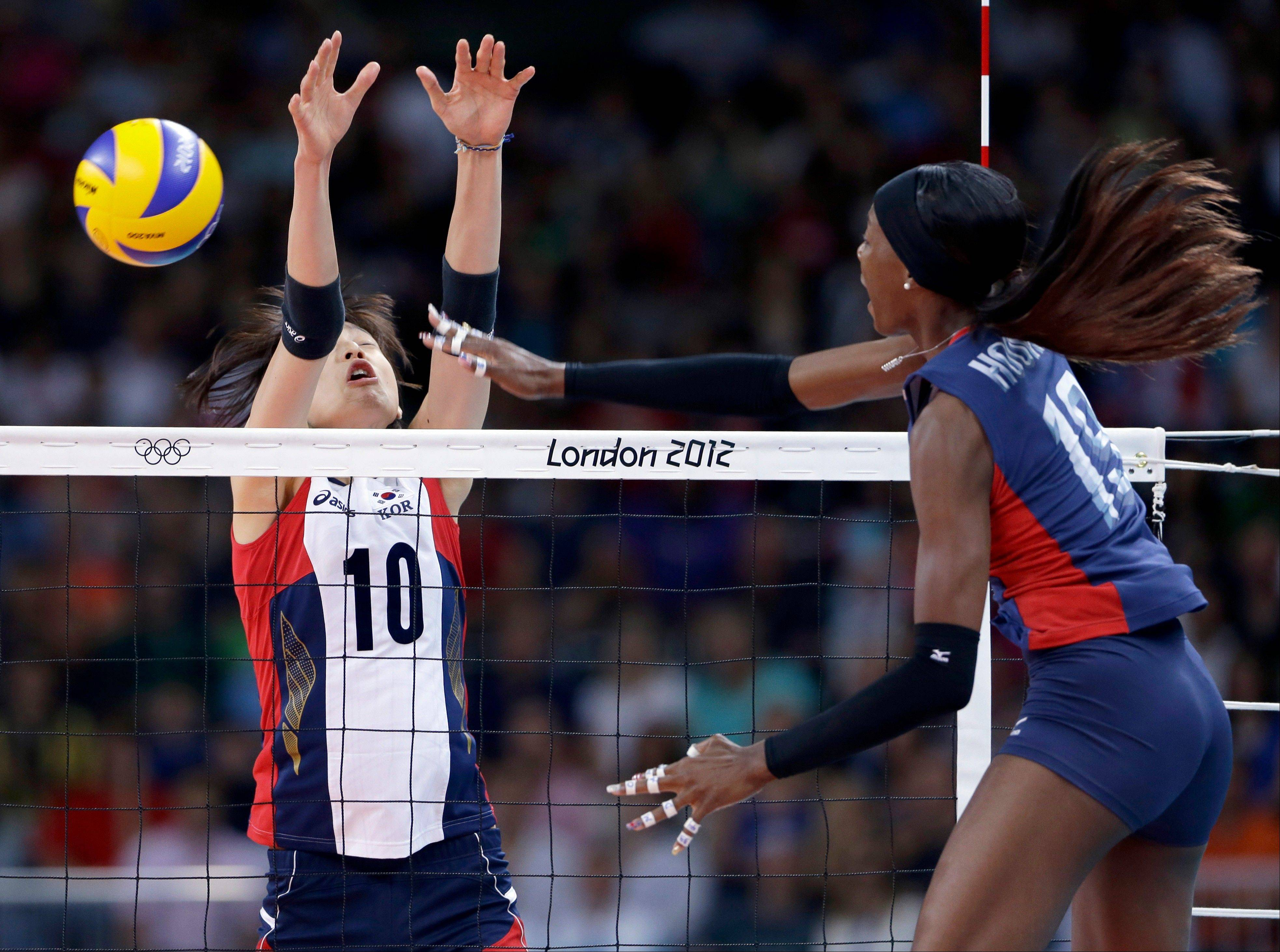 The United States� Destinee Hooker, right, spikes the ball past South Korea�s Kim Yeon-koung during a women�s preliminary volleyball match Saturday at the London Olympics.