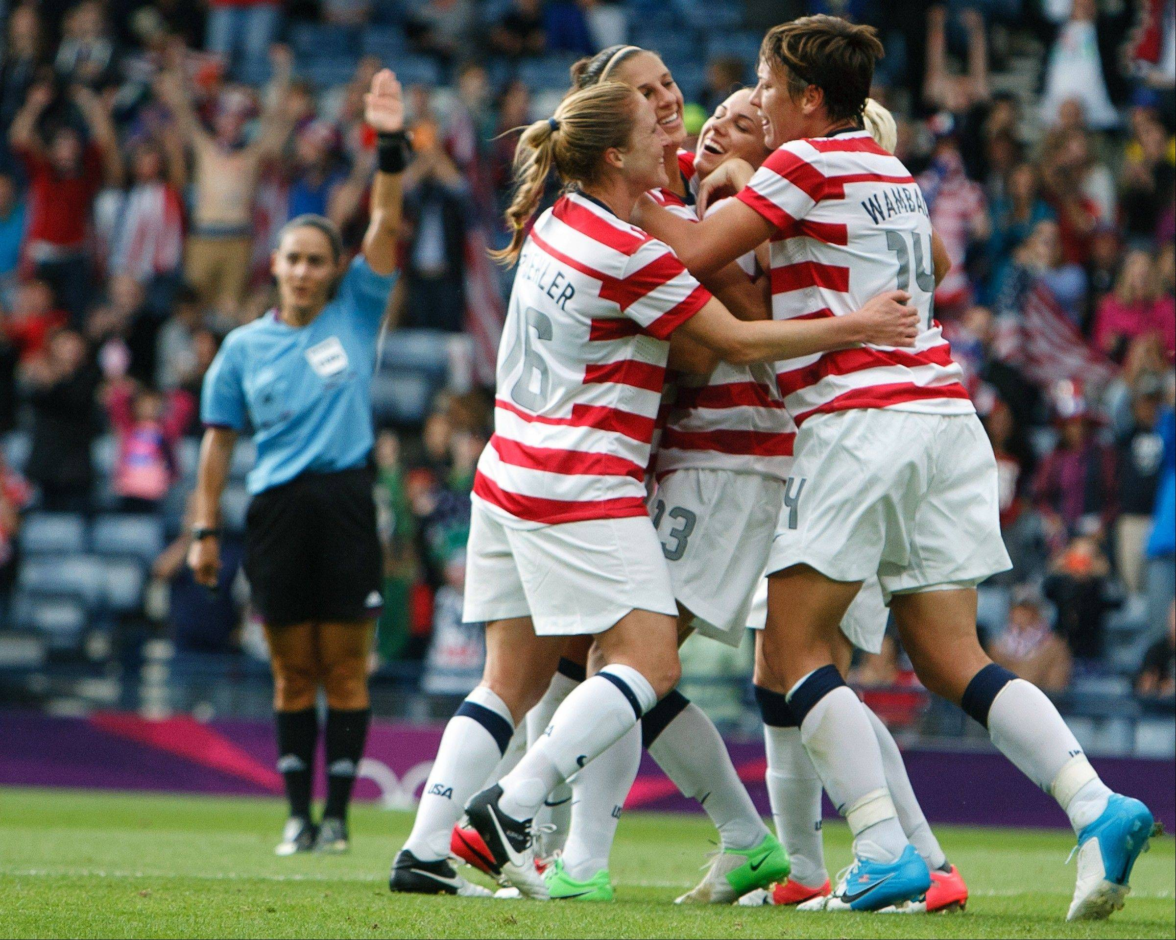 U.S. players celebrate after scoring the opening goal in a match against Colombia on Saturday in Scotland. With the 3-0 win, Team USA advanced to the Olympic quarterfinals.