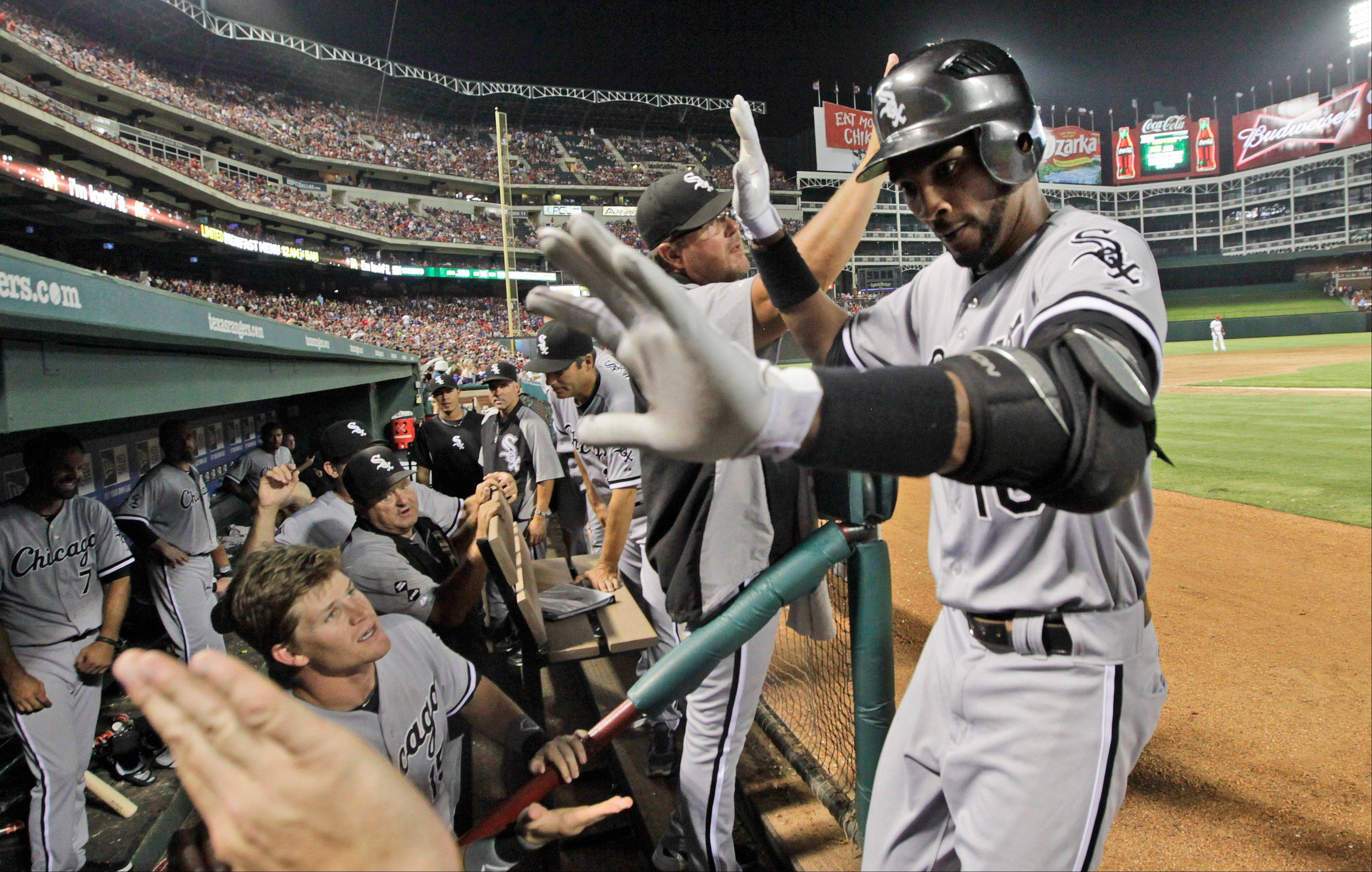 White Sox shortstop Alexei Ramirez, right, is greeted by teammates in the dugout Friday after hitting a 2-run home run during the ninth inning against the Texas Rangers. The White Sox won 9-5.