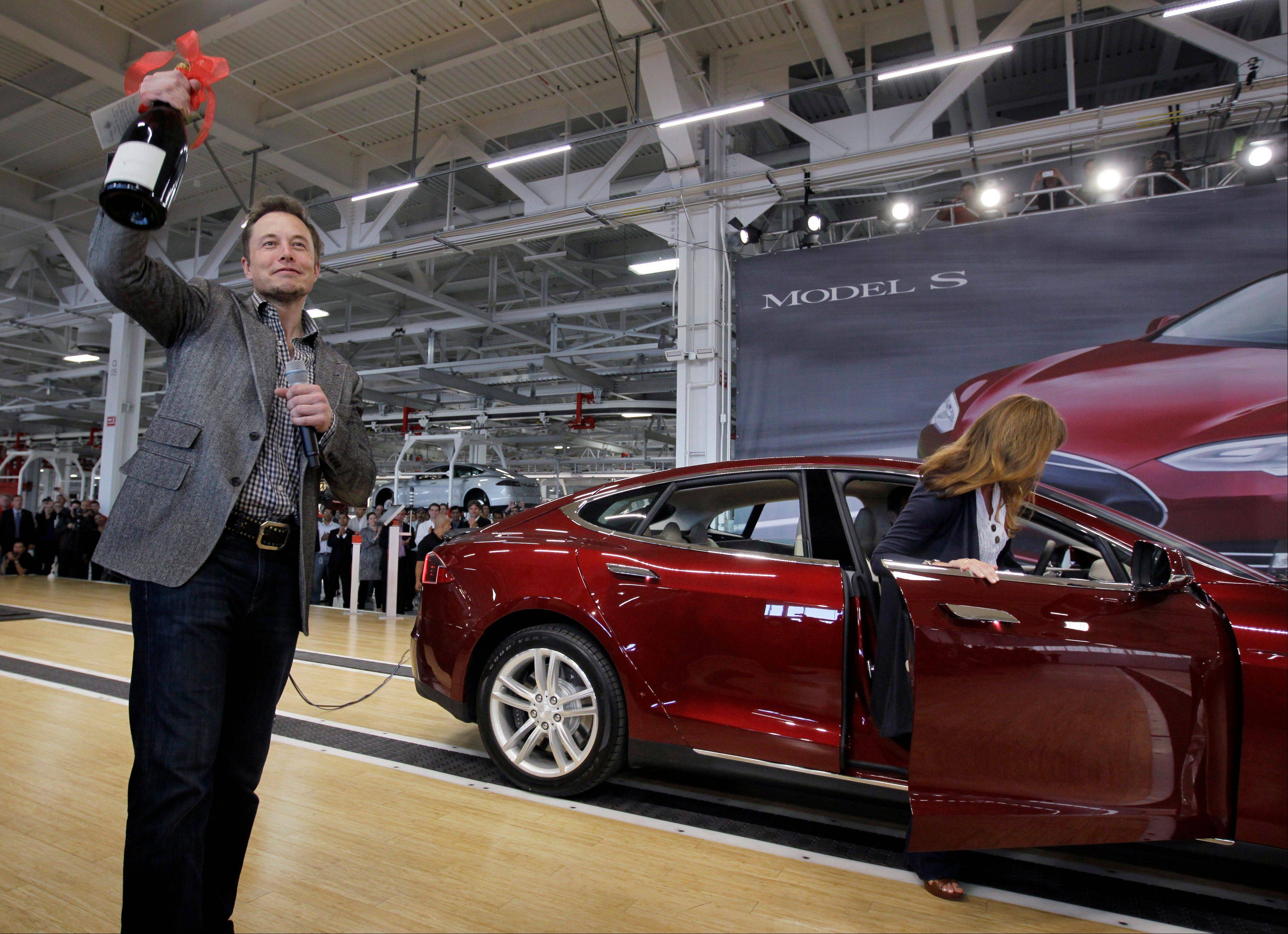 Tesla Motors Inc. CEO Elon Musk holds up a bottle of wine given as a gift from one of their first customers, right, during a rally at the Tesla factory in Fremont, Calif., on June 22. Tesla on Wednesday said that its second-quarter net loss nearly doubled as it invested heavily to launch its second vehicle, the Model S.