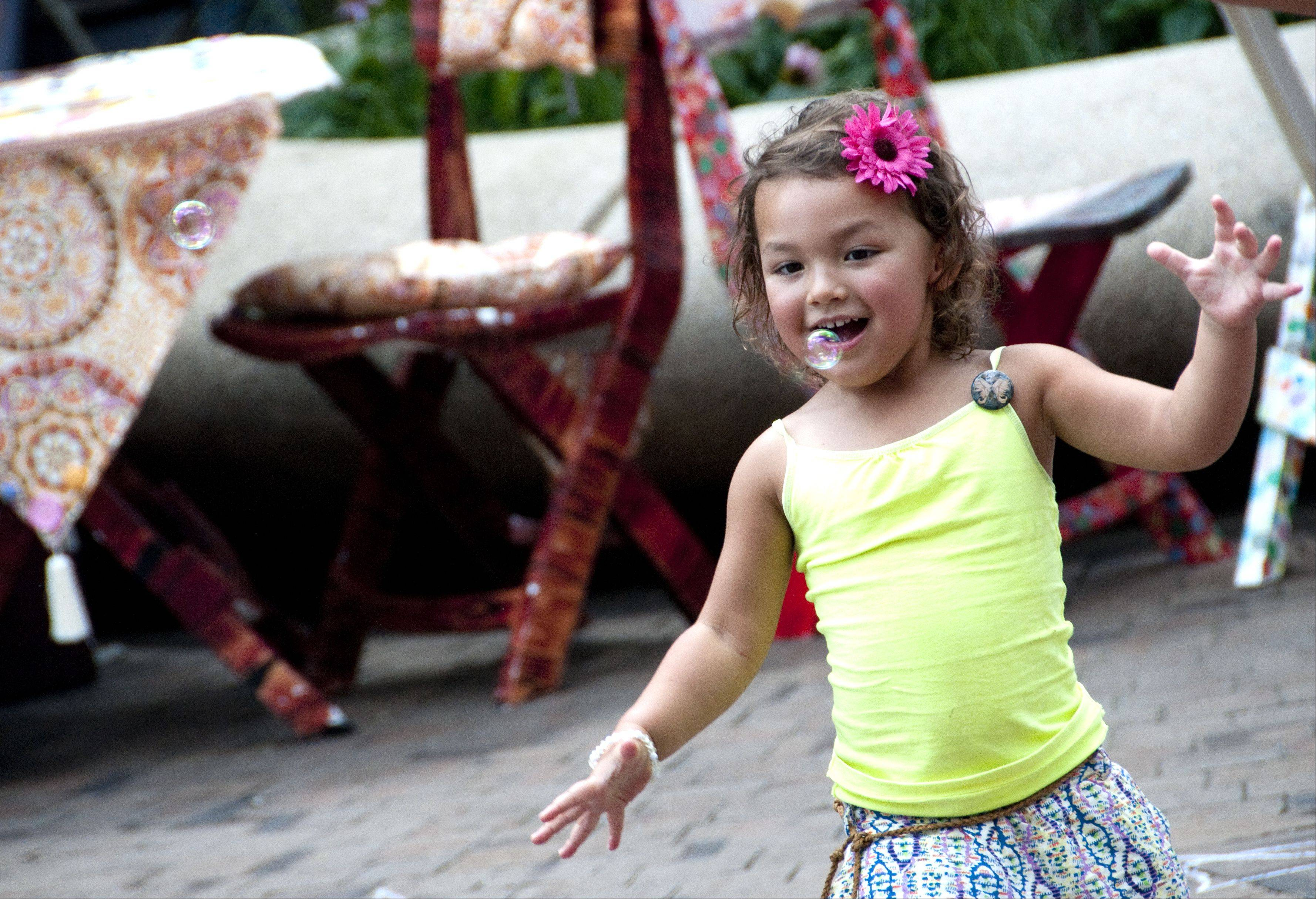 Leyla Garcia, 3, of Pingree Grove, chases bubbles in the food court on Saturday at the Art & Soul on the Fox festival in downtown Elgin. The festival features artists working with a variety of mediums including ceramics, glass, metal, photography, watercolors, wood and more.