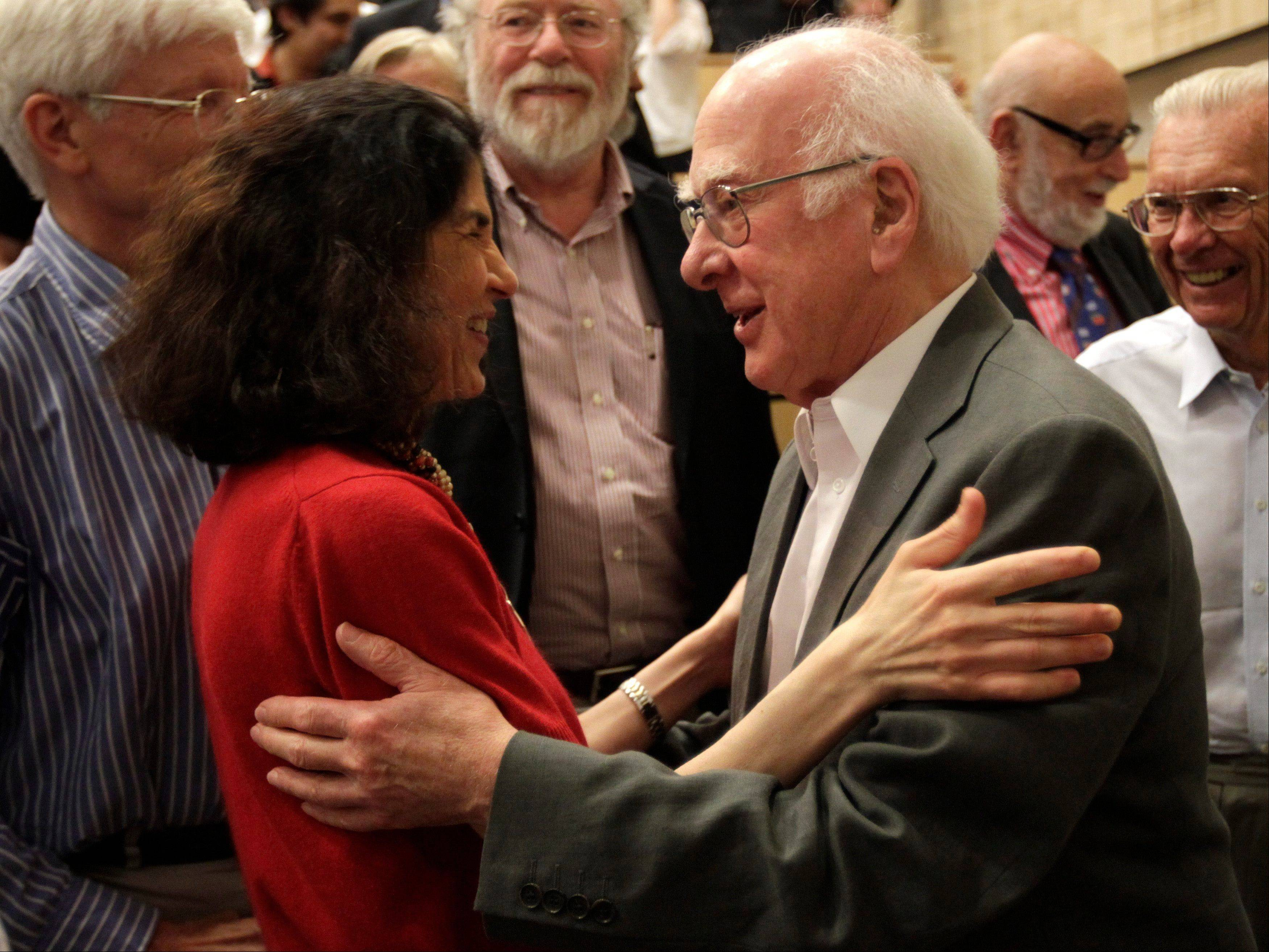 British physicist Peter Higgs congratulates Fabiola Gianotti, ATLAS experiment spokeswoman, after her results presentation during a scientific seminar July 4 to deliver the latest update in the search for the Higgs boson.