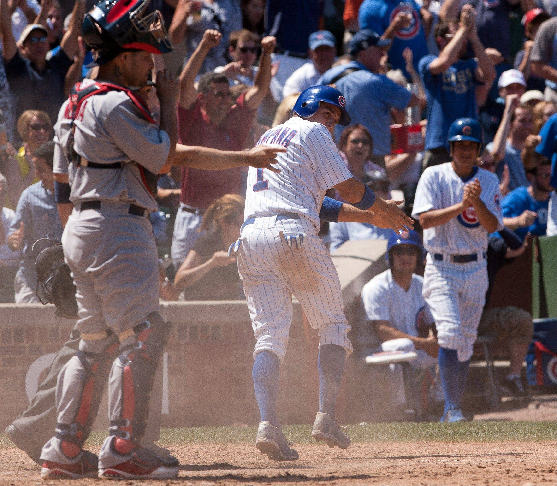 Tony Campana, center, scores what turned out to be the winning run Saturday at Wrigley Field.