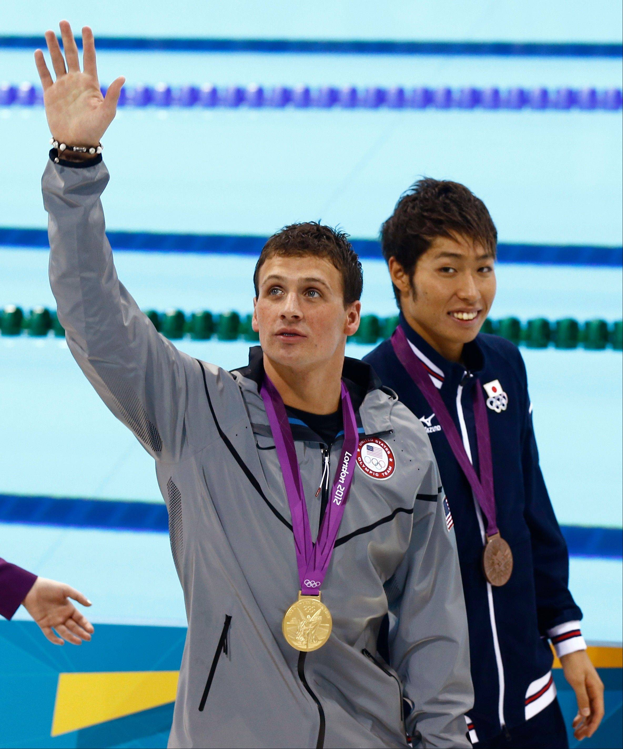 The United States' Ryan Lochte waves during the medal ceremony for men's 400-meter individual medley swimming final Saturday in London. Japan's Kosuke Hagino wears the bronze.