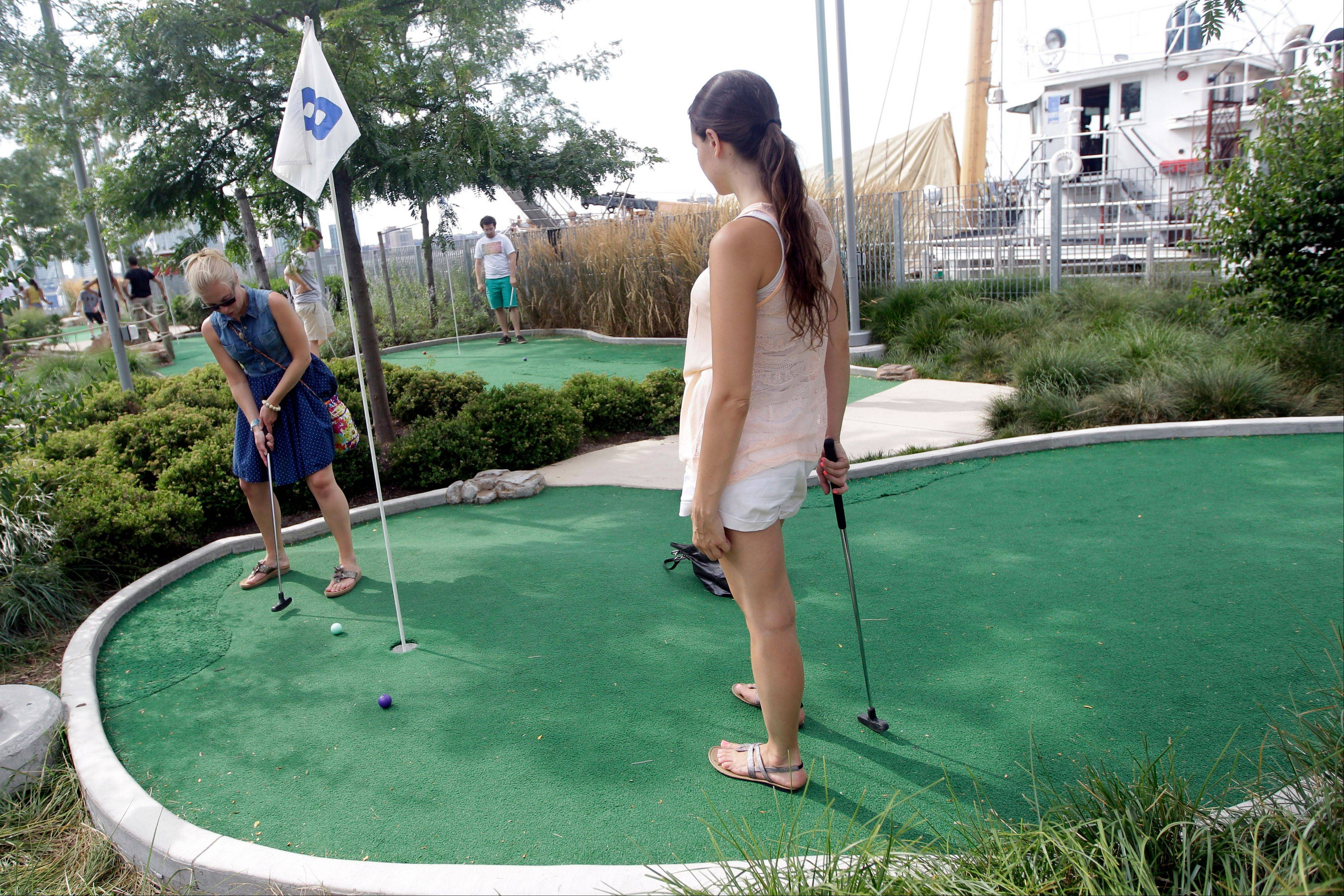 Visitors to the Hudson River Park in New York play miniature golf.