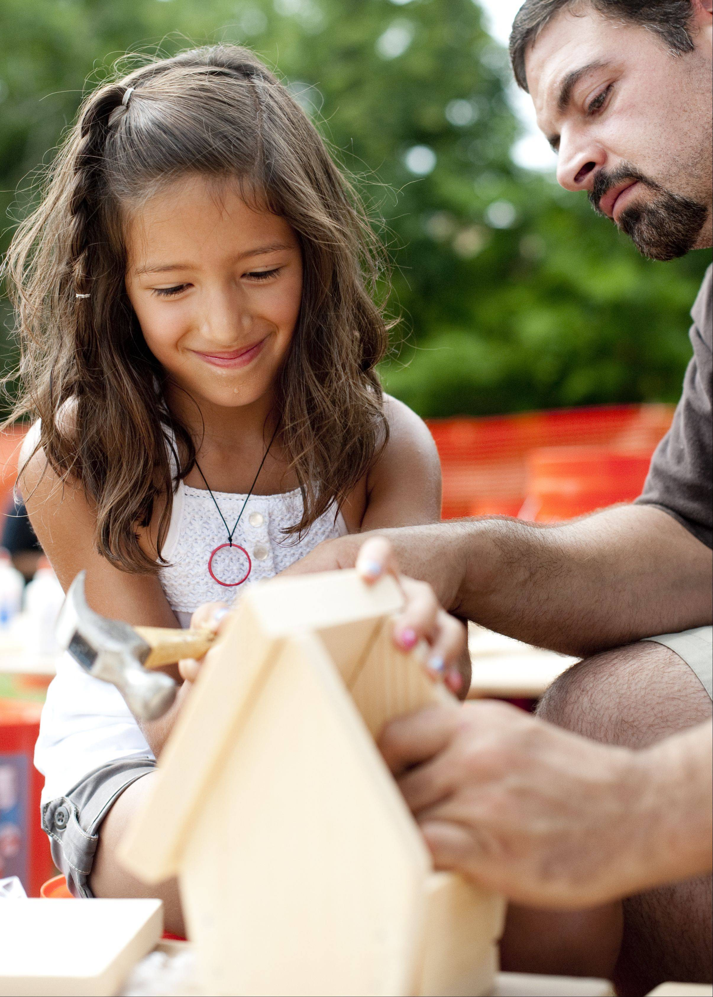 Alexis Celentano, 7, of Cary gets help from her father, David, while putting the roof on a birdhouse in the crafts area of the 52nd Algonquin Founders Days Sunday in Algonquin�s Towne Park.