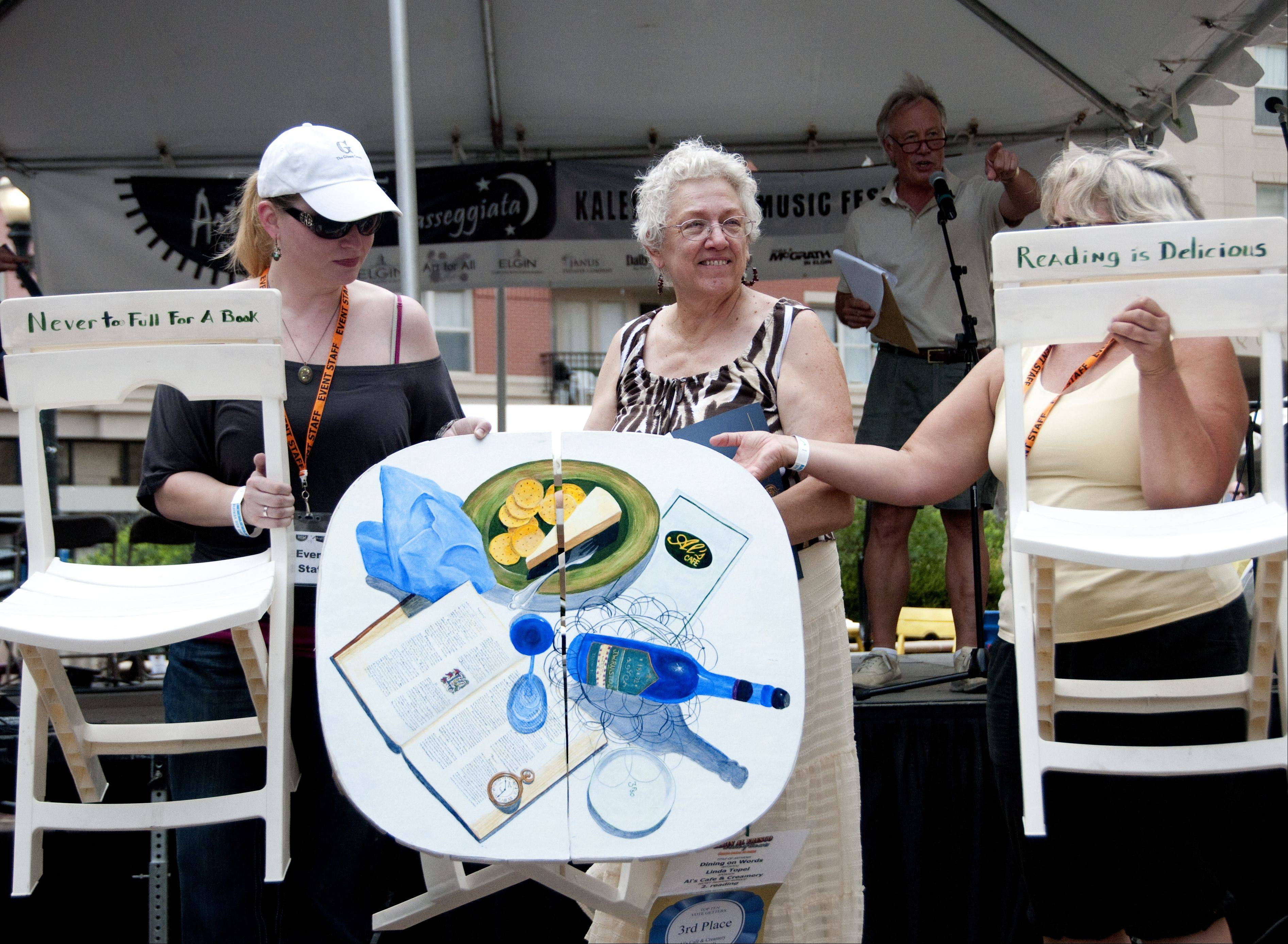 Linda Topel of Bensenville helps auction off her Best in Show decorated table at Day 2 of the Art & Soul on the Fox in Elgin Sunday.