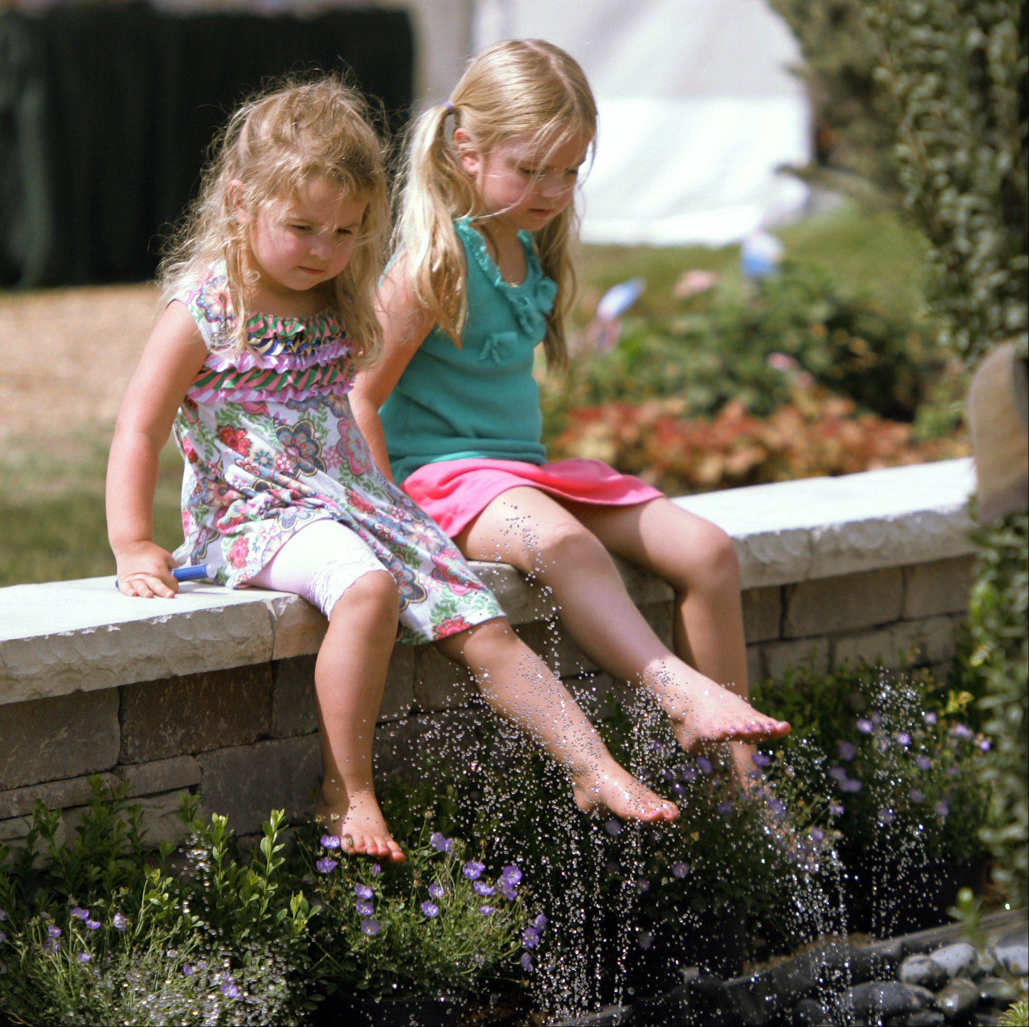 Sisters Audrey, 2, left, and Grace Routh, 5, of Hoffman Estates, play in the sprinklers at the Growing Grace Landscape Association exhibit at the Chicago Flower & Garden Show during the last day of the 84th Annual Lake County Fair Sunday in Grayslake.