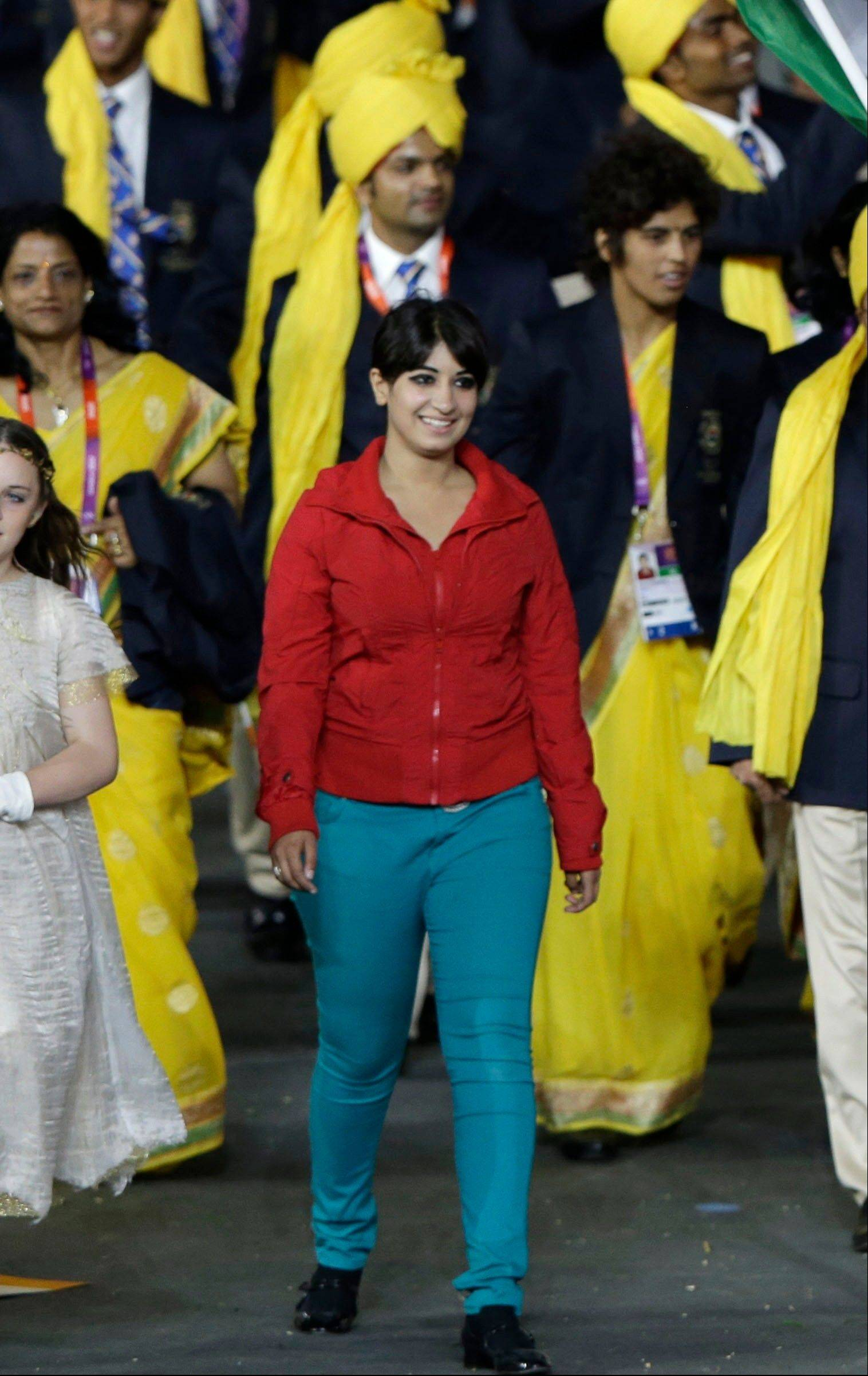The Friday July 27, 2012 photo shows a cast member walking with the Indian team during the Opening Ceremony at the 2012 Summer Olympics, Friday, July 27, 2012, in London. The woman stood out during India's walk through Olympic Stadium at the opening ceremony. That's because she wasn't supposed to be there. Friday night's party crasher was not wearing the yellow and white dress that every other Indian woman was wearing in the group, yet still managed to situate herself next to flag bearer Sushil Kumar at the front of the line as they walked around the stadium.