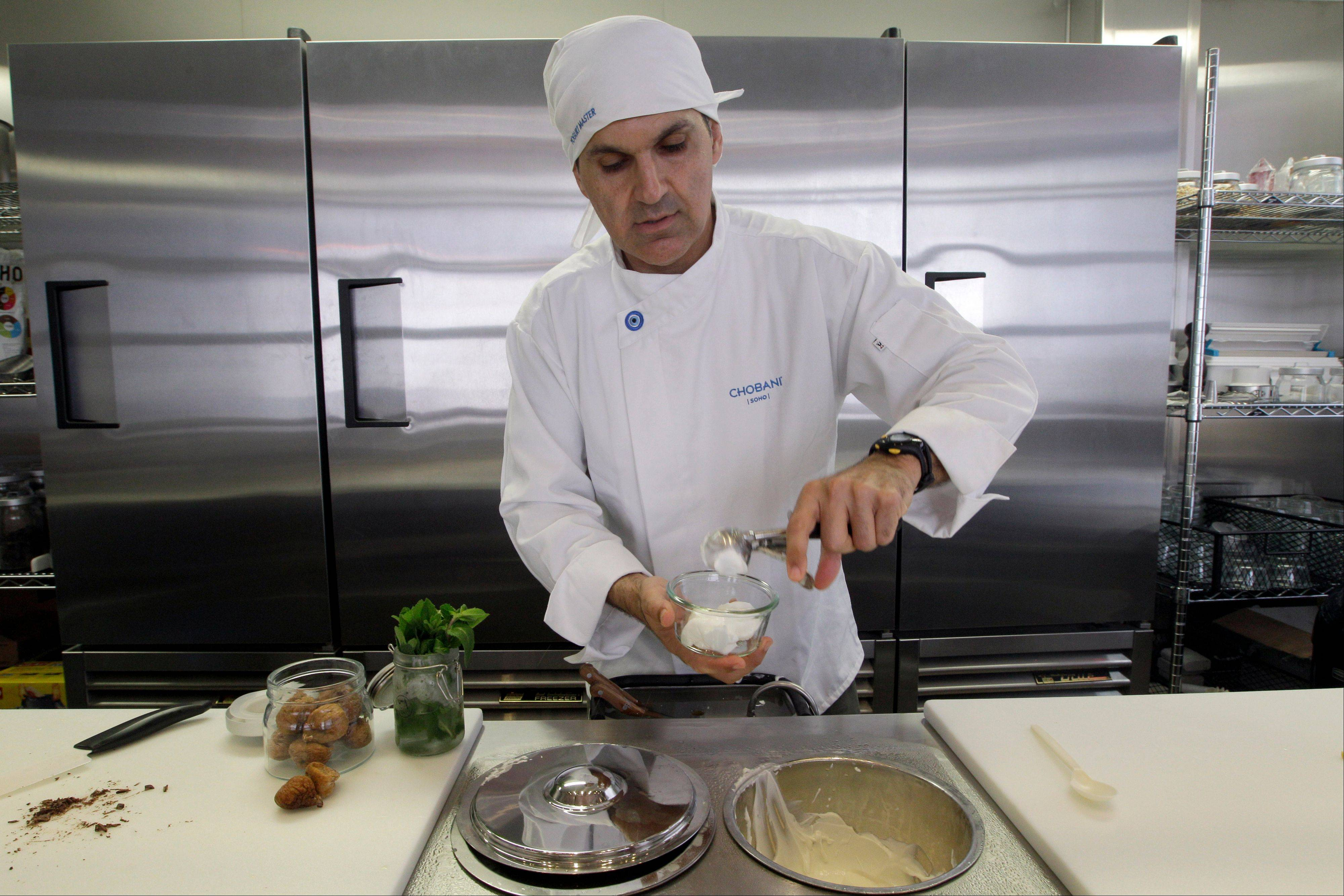 "Dar Vasseghi, director of retail concepts at Chobani, prepares one of the bar's creations at the Chobani yogurt bar in the Soho neighborhood of New York on July 23. Chobani, opened its first ""yogurt bar"" in New York City on Wednesday as it looks to strengthen its position in a rapidly growing market."