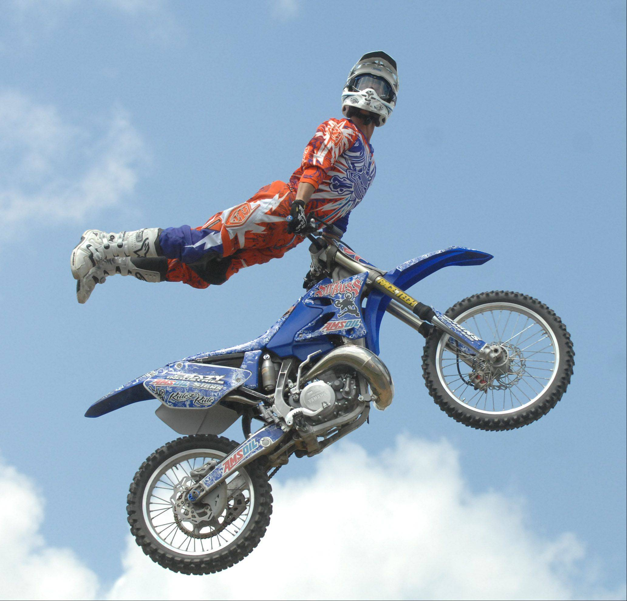 One of five riders in a U.S. FMX Championship Series motocross competition pulls a trick as he glances toward the crowd Saturday at the DuPage County Fair in Wheaton.