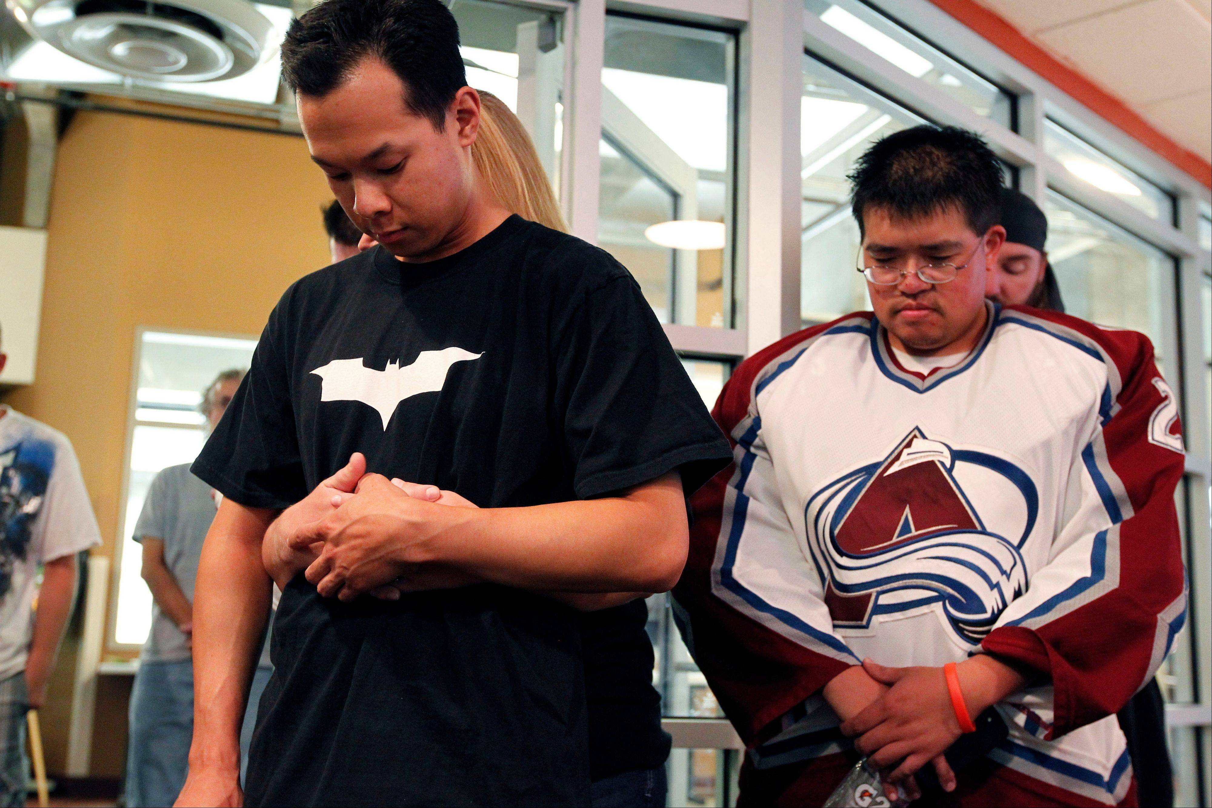 Joey Suyeishi, left, wears a bat T-shirt and is held by his wife Heidi Suyeishi, as they and others hold a moment of silence to honor Jessica Ghawi in the Penalty Box Bar during a fund raising event at the Edge Ice Arena, Saturday in Littleton, Colo. Ghawi was one of the 12 people killed in the July 20 shooting attack.
