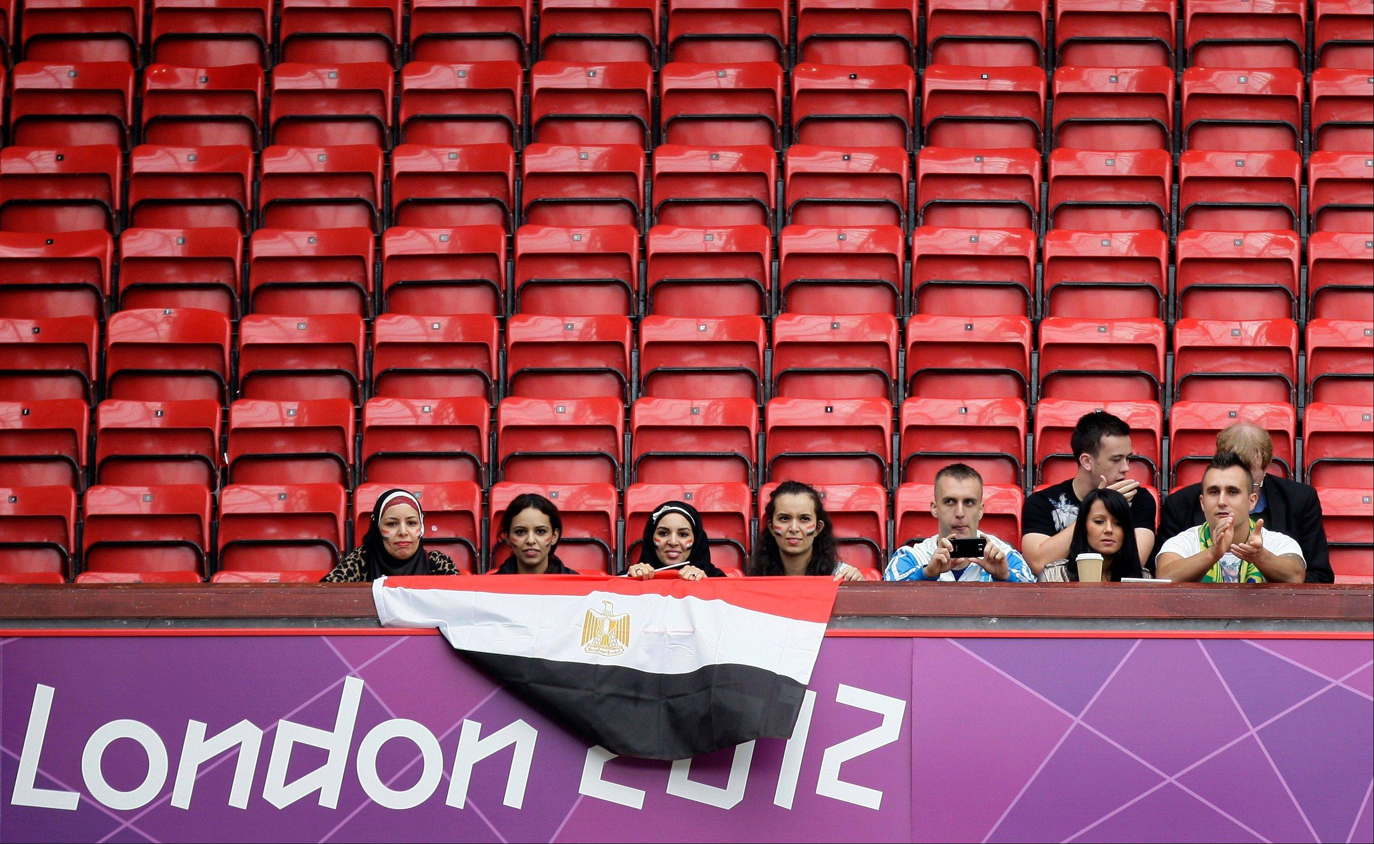 Spectators sit amongst empty seats before Egypt's group C men's soccer match against New Zealand at the London 2012 Summer Olympics, Sunday at Old Trafford Stadium in Manchester, England.