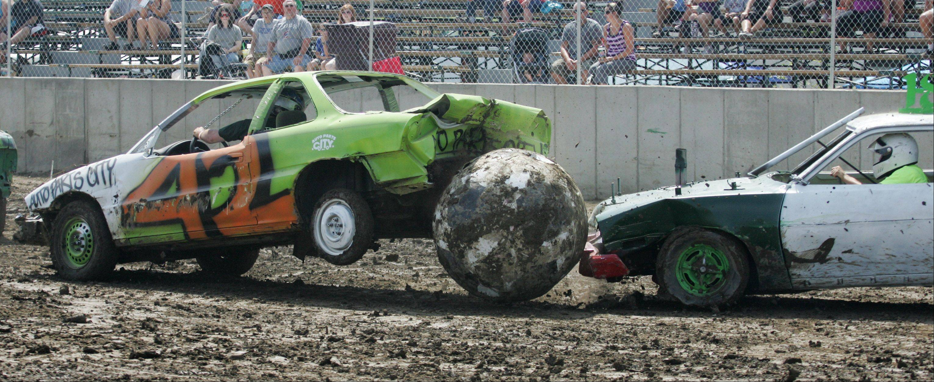 Team USA driver Gary Rogers, left, has his car lifted off the ground as Team Italy driver Scott Redden rams the ball into him during Auto Soccer at the Lake County Fair Sunday in Grayslake. Team USA won the contest 4-0.