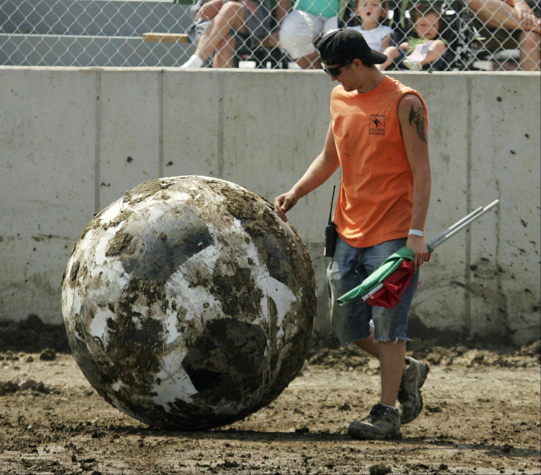 Flagman Zach Lentz moves the 400 lb. ball to the middle of the field during Auto Soccer at the Lake County Fair Sunday in Grayslake.