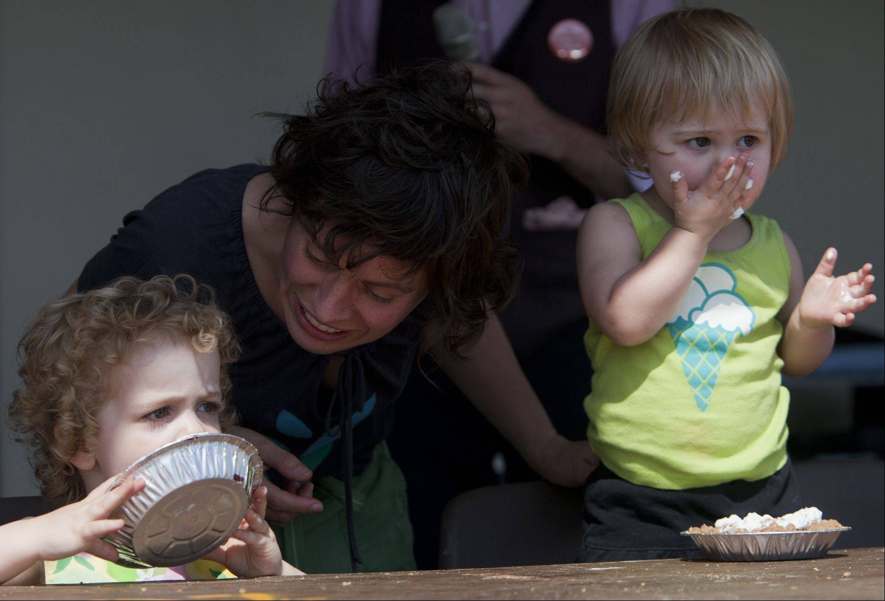 Anastasia Masurat of Chicago encourages Estelle, 2, and LuLu, 1, Cannahan to eat a blueberry pie during an old-fashioned pie eating contest in which contestants had five minutes to eat the most at the Lake County Fair on Saturday at the Lake County Fair on Saturday.