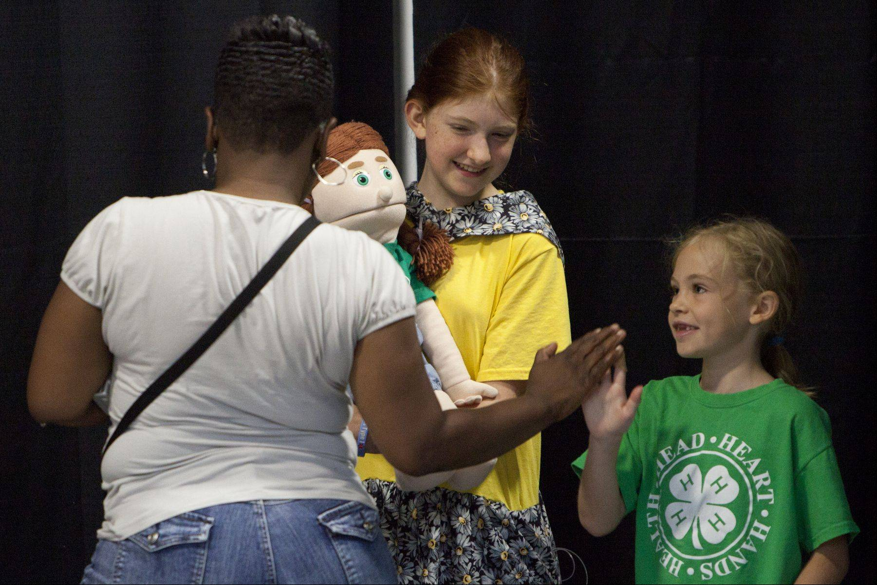4H Community worker Sabrina Huley gives Clover Buddy Elena Hevrdejs, 8, of Lake Villa a high-five and Kit Brennes after participating in the 4H fashion show at the Lake County Fair on Saturday