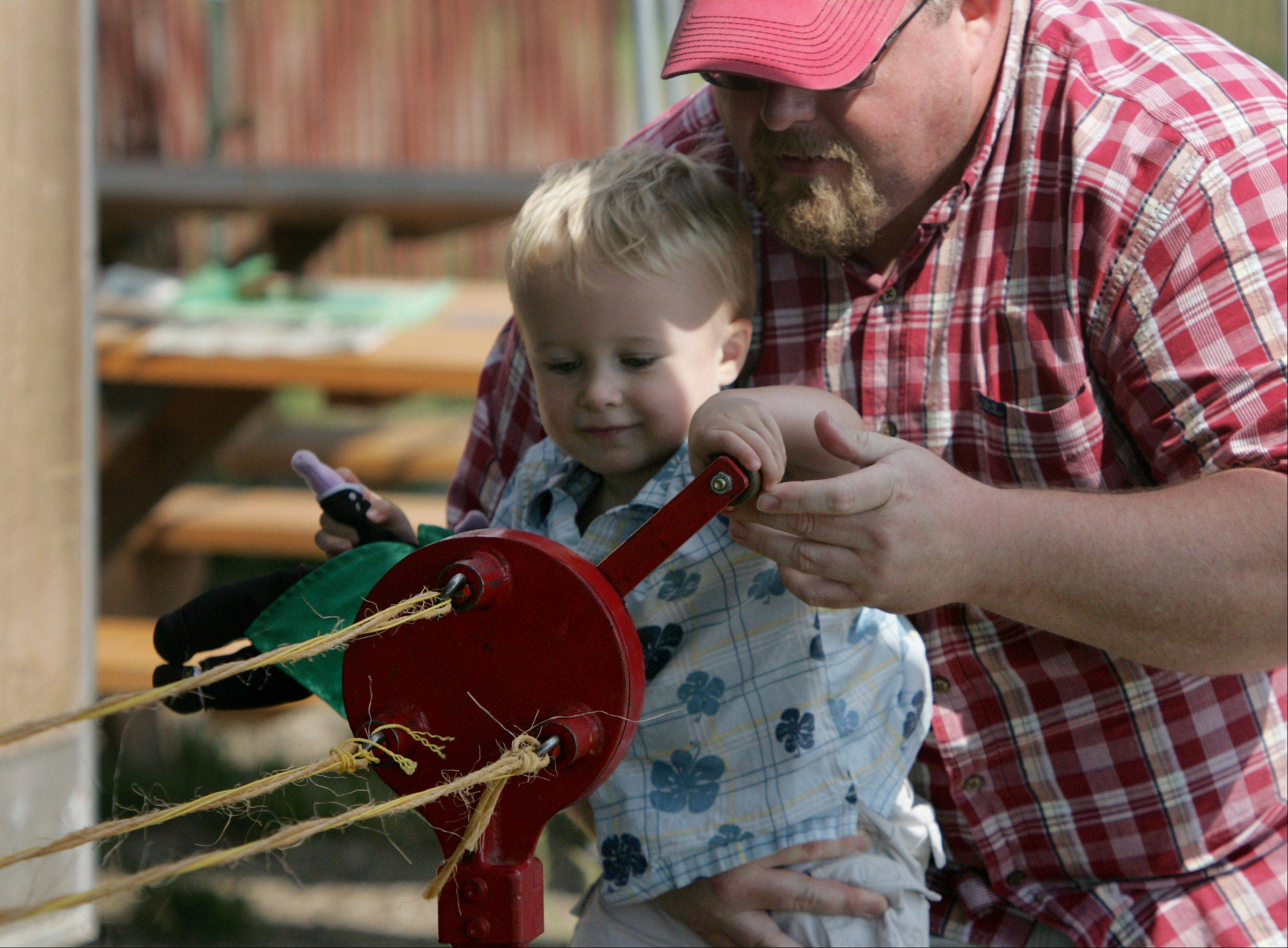 David Martin, of McHenry, holds his son, Isaac, 2, as they spin rope during last day of the 84th Annual Lake County Fair Sunday in Grayslake.