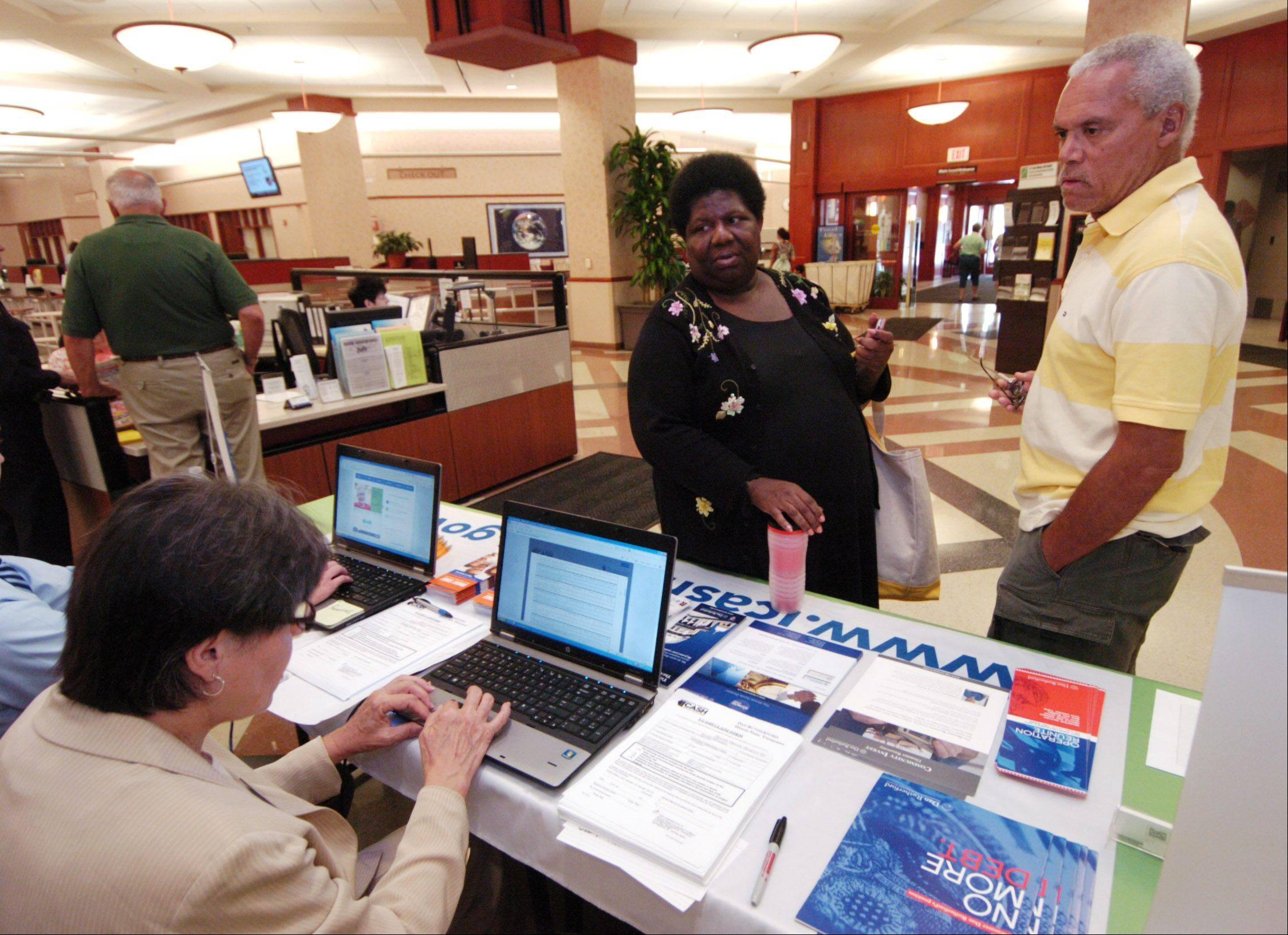 With the assistance of state Treasury Department marketing representative Barbara Chalko, seated, Jacqueline and William Rogers of Schaumburg check for unclaimed property through use of the I-Cash program website at the Schaumburg library.
