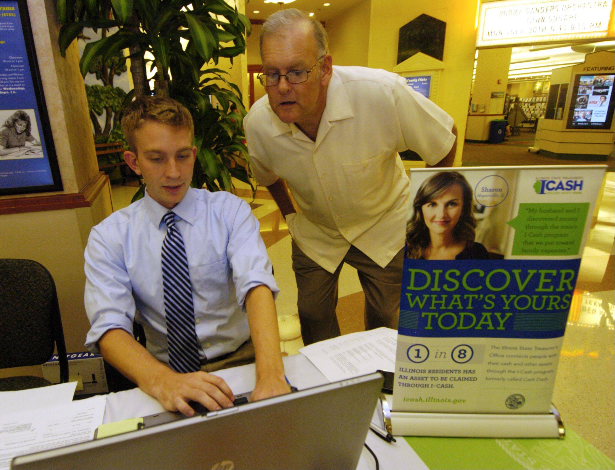 Alex Giesick, left, an intern with the state treasurer's office, assists Schaumburg Township Clerk Tim Henneghan as he checks for unclaimed property through use of the I-Cash program website.