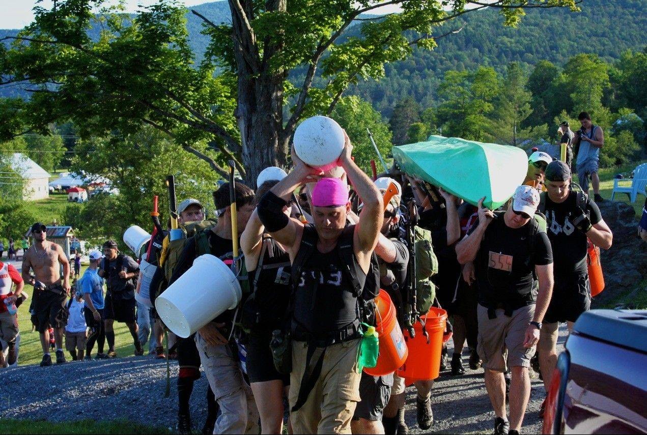 Racers in the Spartan Death Race in Vermont carry water-filled plumbing pipes, kayaks and tractor tires over their heads as part of a 25-mile hike challenge.