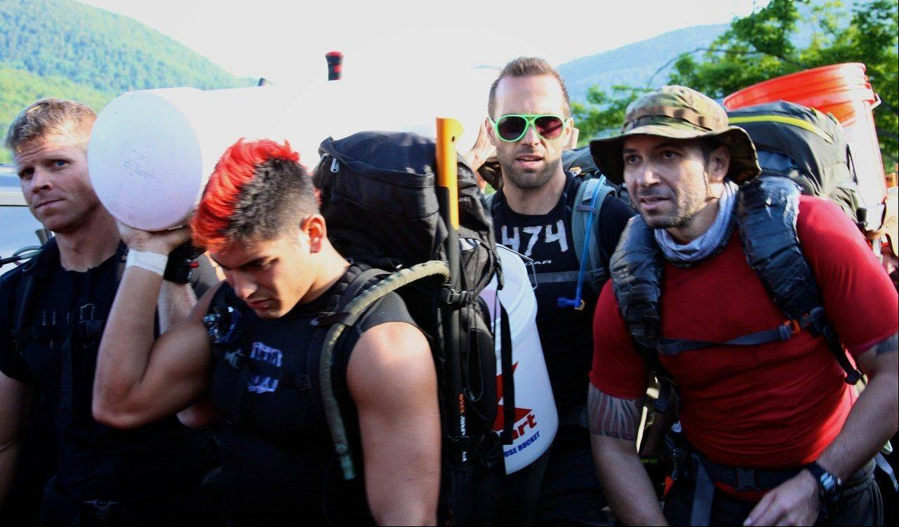 Contestants in the Spartan Death Race carry a water-filled plumbing pipe as they embark on a 25-mile hike.
