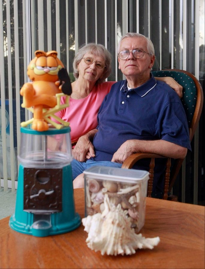 JoAnn Zywicki, left, and her husband, Hank, pose on July 17 with a Garfield bubble gum bank and seashells that once belonged to their daughter Tammy at their home in Ocala, Fla. Two decades after Tammy was found stabbed to death along an Illinois highway while returning to college in Iowa, the case remains unsolved.