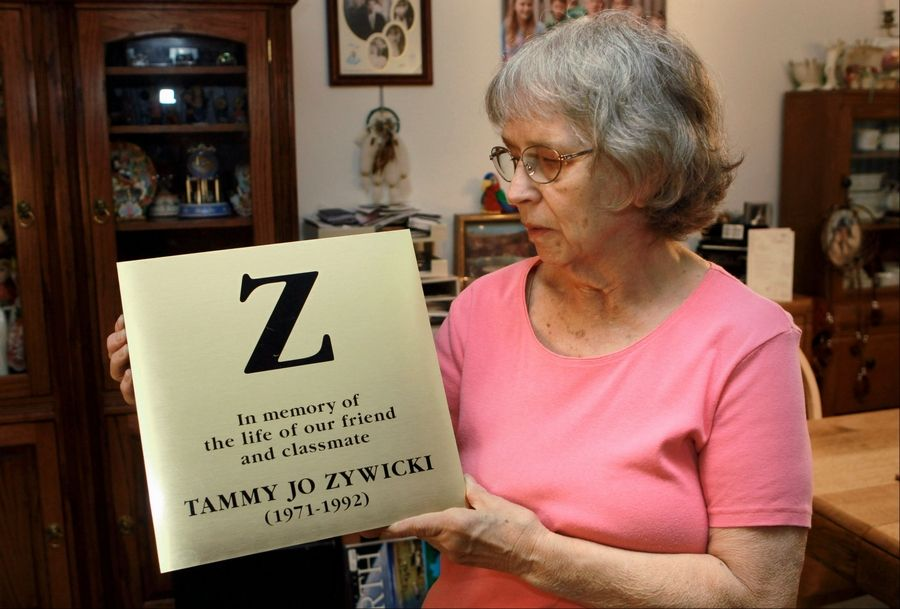 JoAnn Zywicki is seen July 17 at her home in Ocala, Fla., holding a marker identical to one on display at Grinnell College in Iowa. Two decades after her daughter Tammy was stabbed to death along an Illinois highway while returning to college in Iowa, the case remains unsolved.