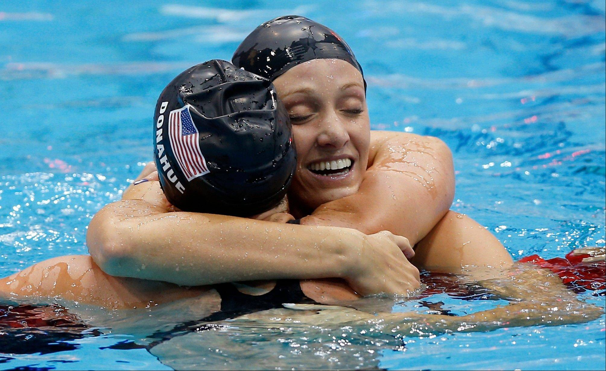 United States swimmer Dana Vollmer embraces teammate Claire Donahue after Vollmer's gold medal win in the he women's 100-meter butterfly swimming final at the Aquatics Centre in the Olympic Park during the 2012 Summer Olympics in London, Sunday.
