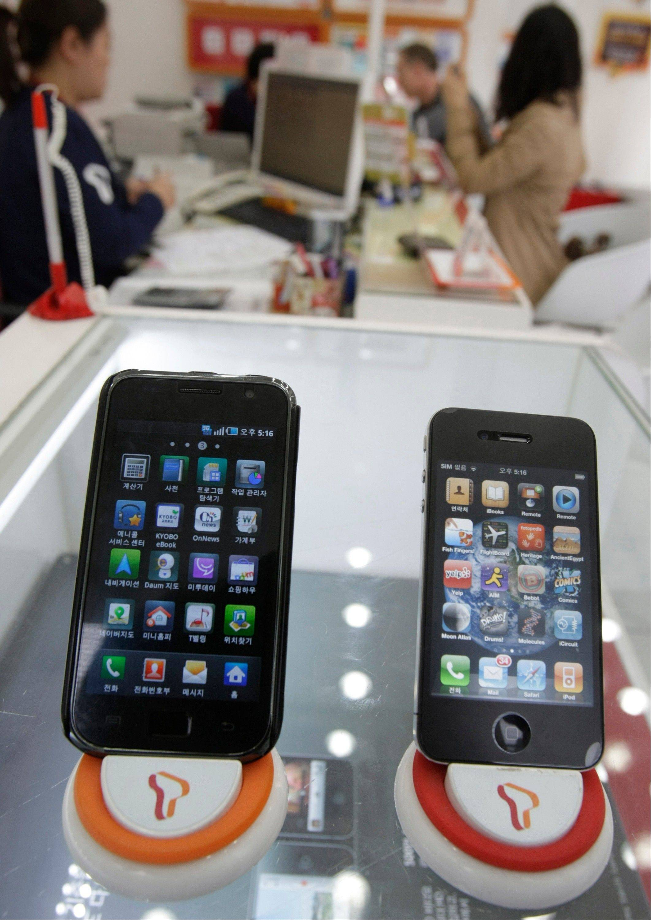 Samsung Electronics� Galaxy S, left, and Apple�s iPhone 4 are displayed at a mobile phone shop in Seoul, South Korea.