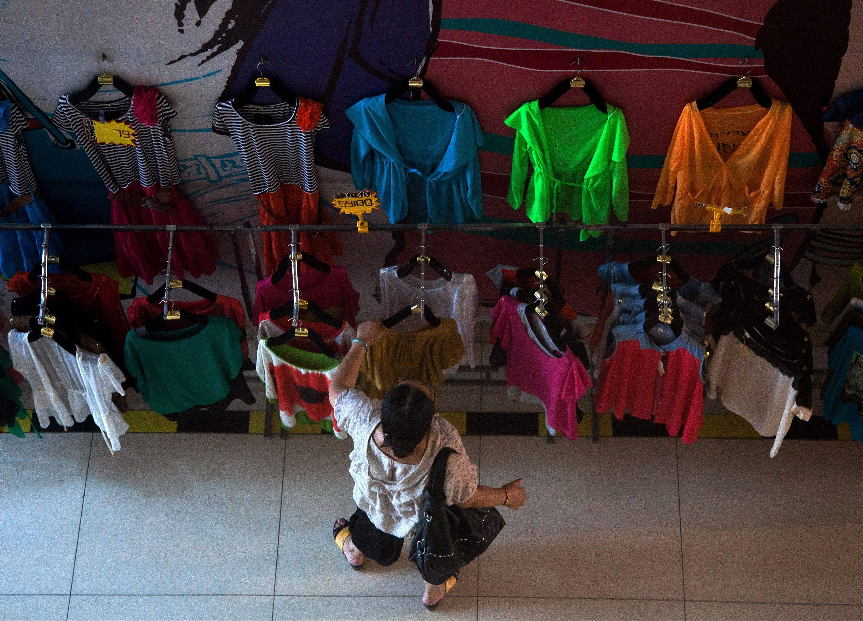 A woman selects fashion clothes hanging for sale at a shopping mall in Beijing, China Sunday.