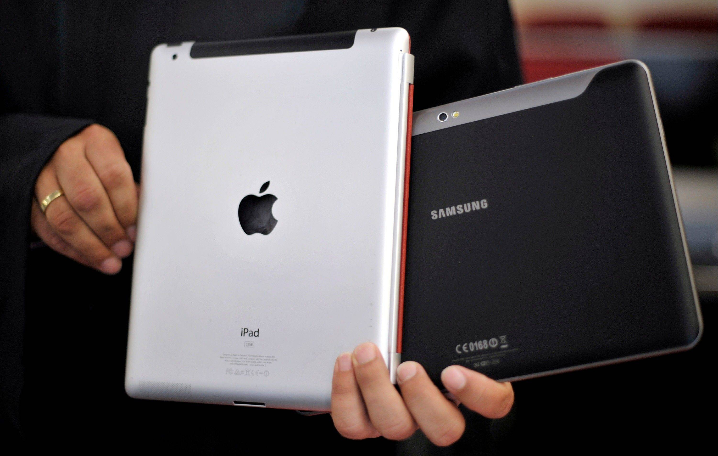 An attorney holds an Apple iPad, left, and a Samsung Galaxy Tab 10.1 at the regional court in Duesseldorf, Germany. The two tech Titans are squaring off in federal court.