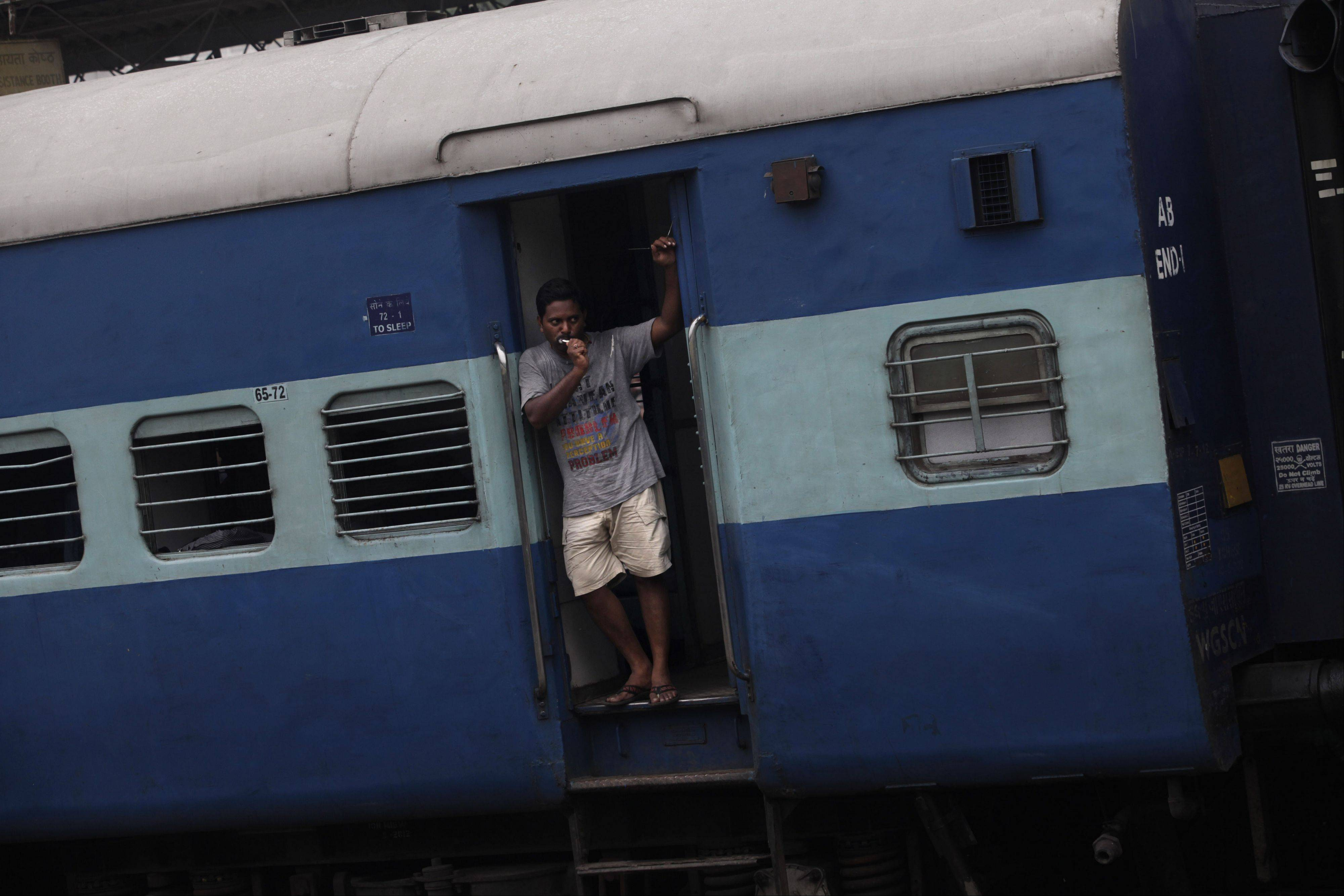 A stranded passenger brushes his teeth at the door of a stationary train compartment following the power outage that struck in the early hours of Monday at a train station in New Delhi, India. A major power outage struck northern India, plunging cities into darkness and stranding hundreds of thousands of commuters.