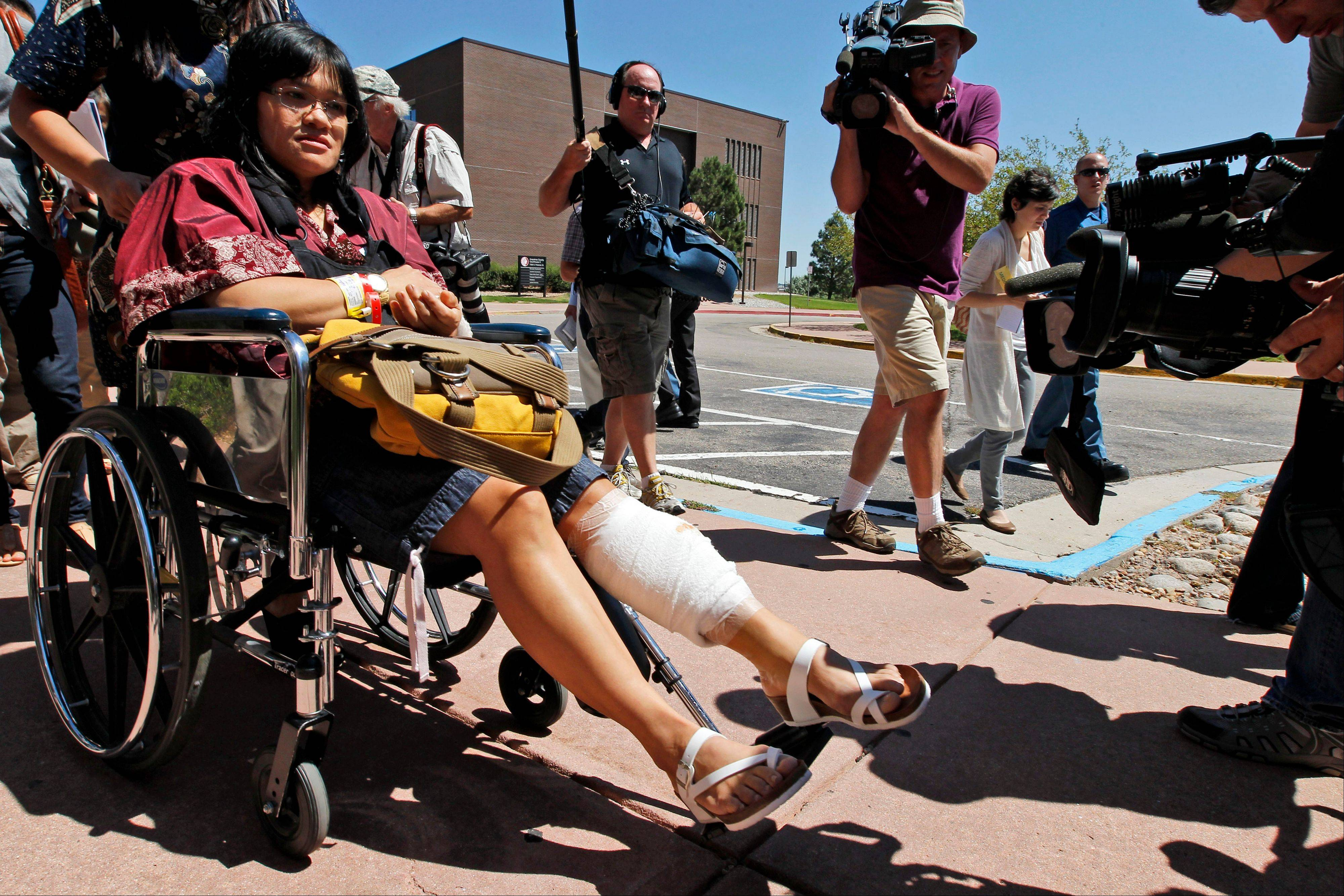 Rita Paulina, in wheelchair, who was injured in the attack, departs the Arapahoe County Courthouse after an arraignment hearing for the accused theater shooter Monday in Centennial, Colo. Colorado prosecutors filed formal charges Monday against the former neuroscience student accused of killing 12 people and wounding 58 others at a movie theater.
