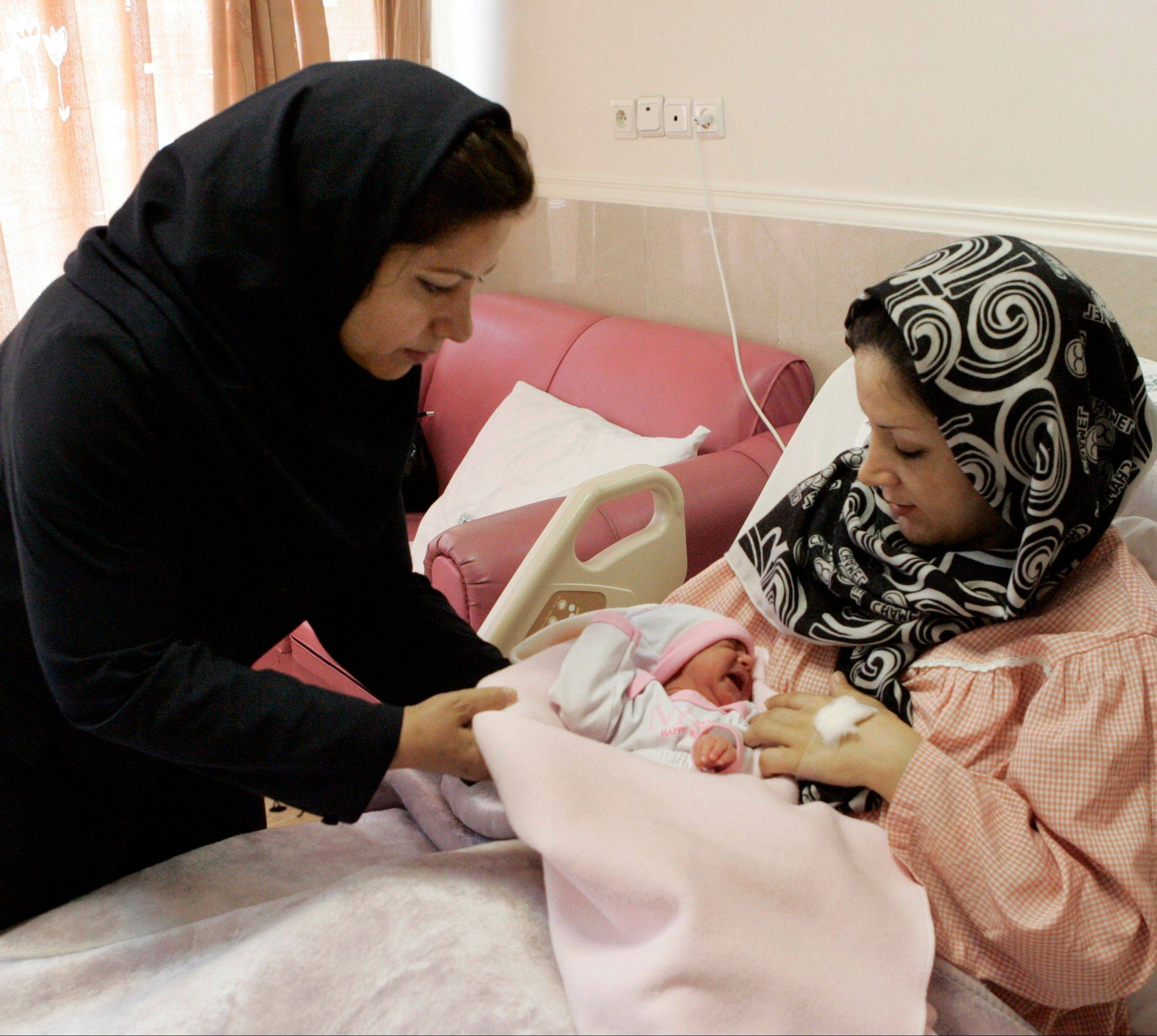 Iranian nurse Zahra Akbarzadeh, left, gives one-day-old baby girl Setayesh to her mother, Tayyebeh Sadat Bidaki, to feed her at the Mehr hospital, in Tehran, Sunday.