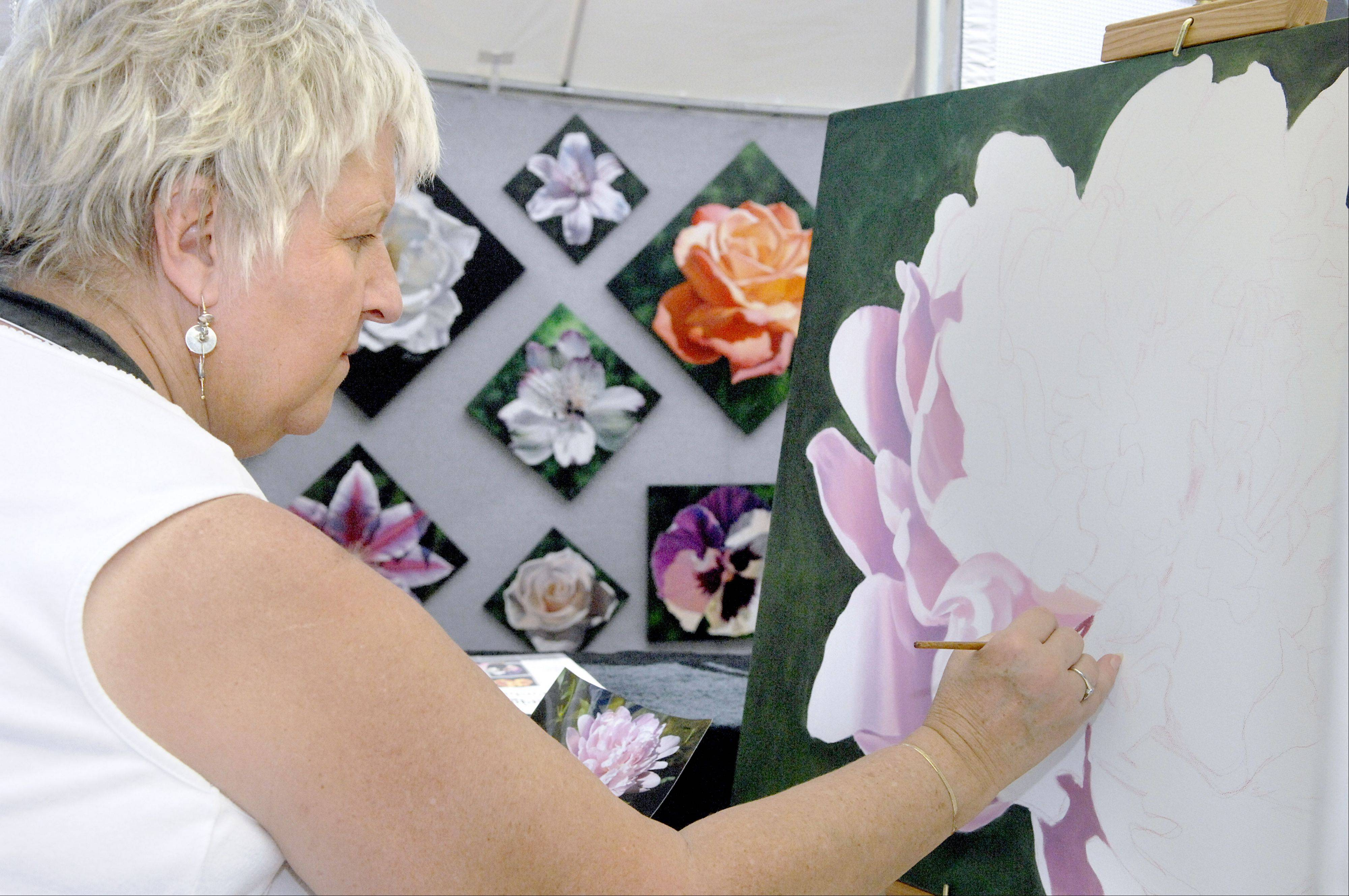 Marge Hall of Winfield paints a new oil piece of a peony at the Geneva Arts Fair on Third Street on Saturday, July 28. Hall has been doing the Geneva show for several years.