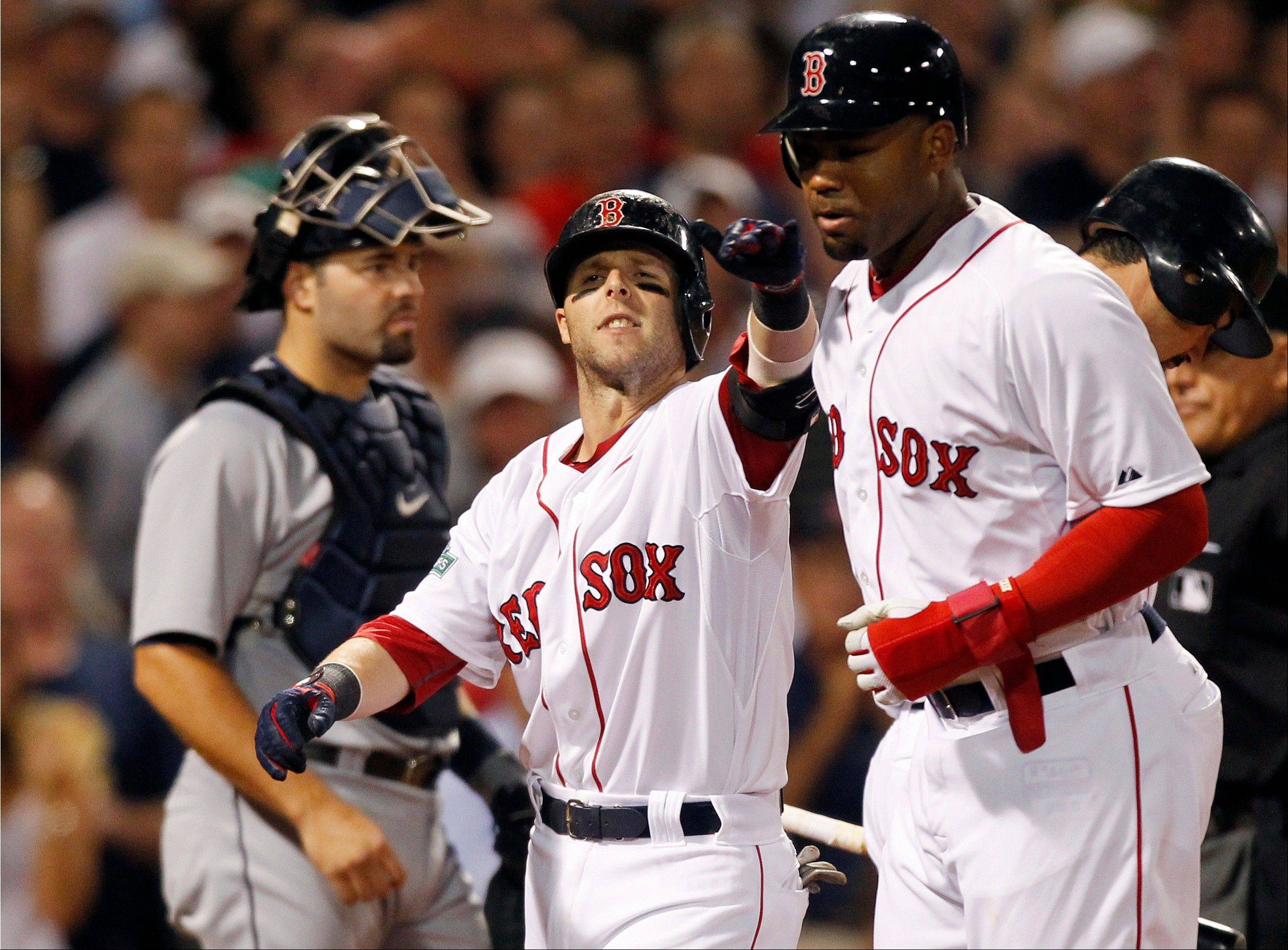 Boston�s Dustin Pedroia, center, celebrates his two-run home run that drove in Carl Crawford, right, in the sixth inning Monday at home against Detroit.