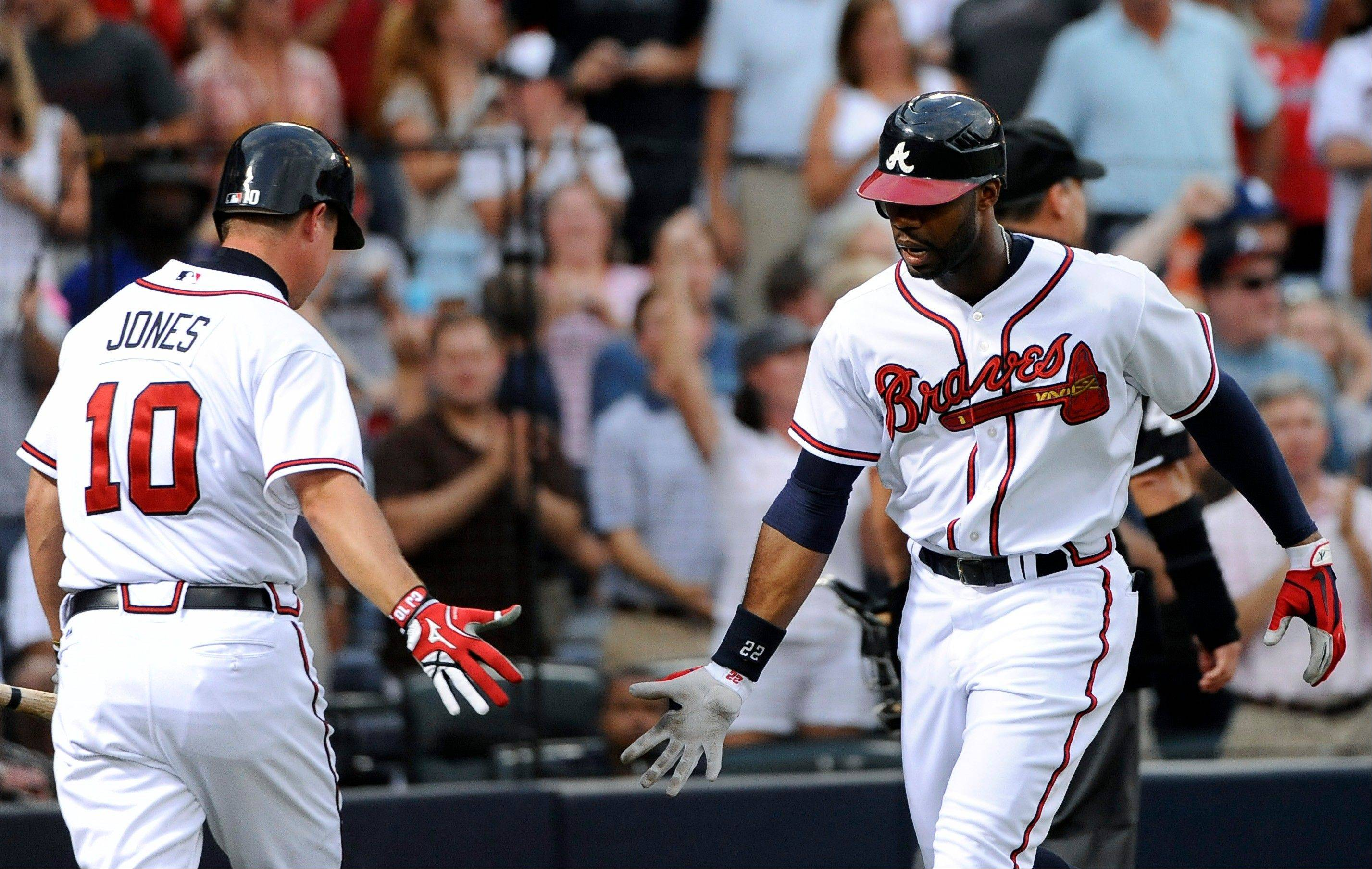 The Braves� Chipper Jones congratulates Jason Heyward on his solo home run against the Miami Marlins during the third inning Monday in Atlanta.