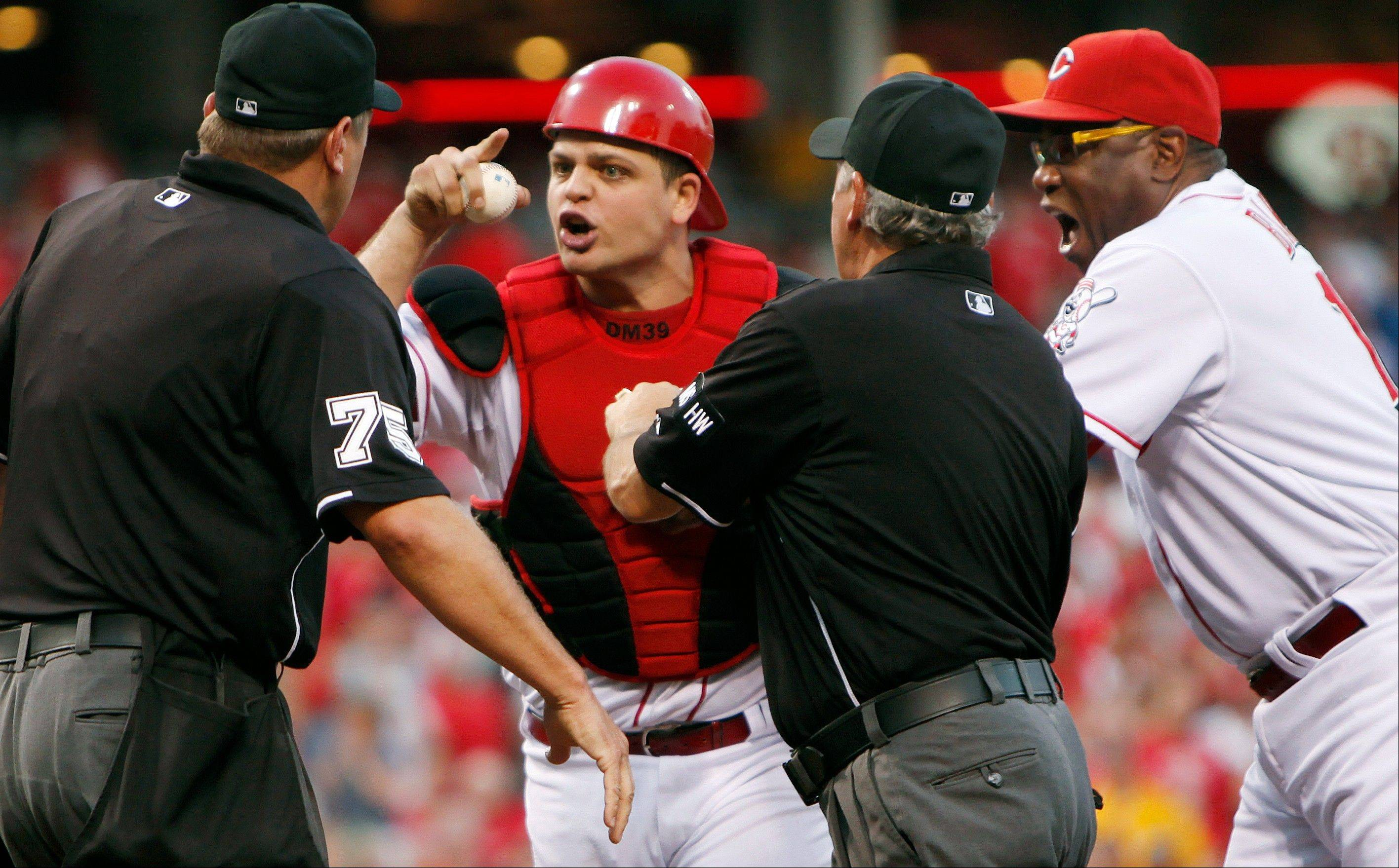 Reds catcher Devin Mesoraco yells at home plate umpire Chad Fairchild as head coach Dusty Baker, right, steps in to pull him back after Mesoraco was ejected for arguing balls and strikes in the third inning Monday at home