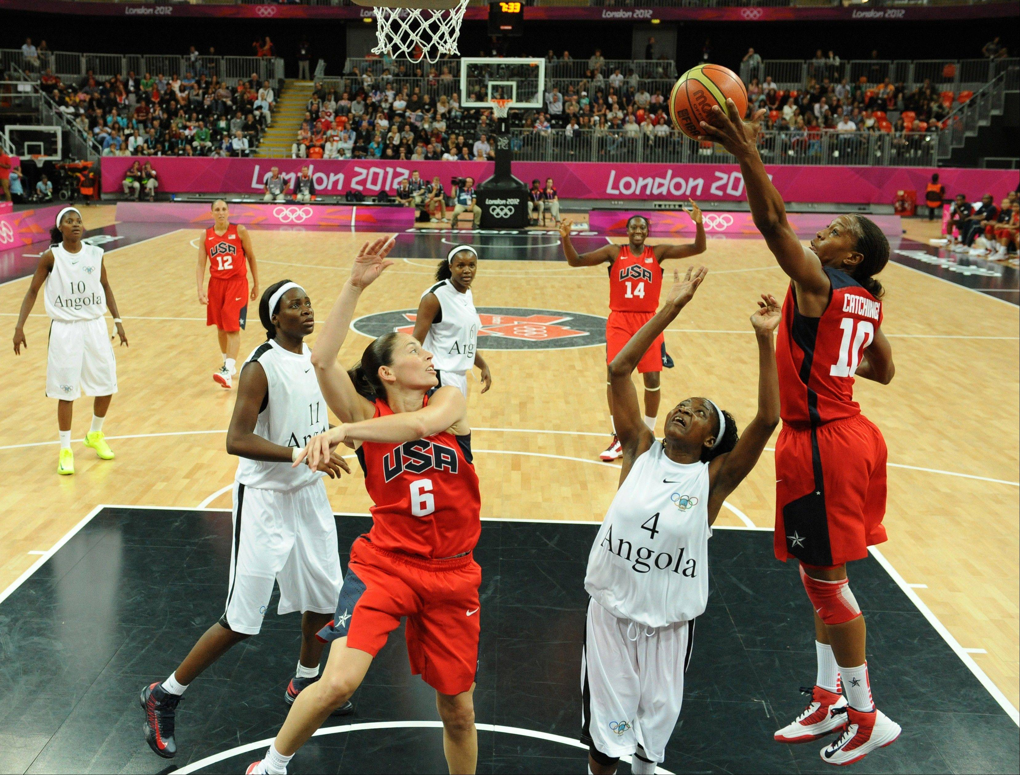 United States� forward and Stevenson High School grad Tamika Catchings, right, and guard Sue Bird, center, vie for the ball with Angola�s guard Catarina Camufal, second from right, during Monday�s women�s preliminary round group A basketball match at the 2012 Summer Olympics.