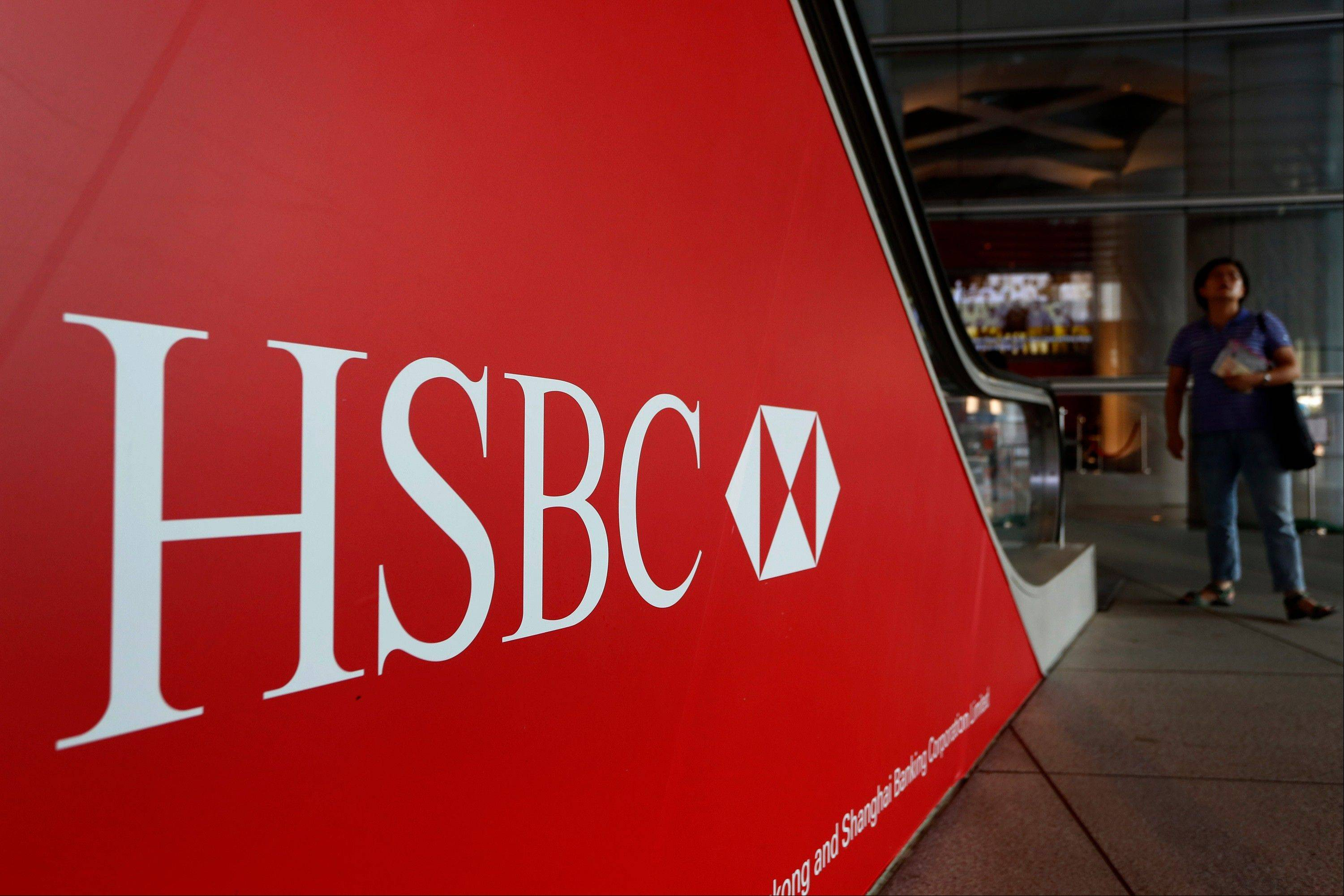 People walk past a logo of HSBC headquarters in Hong Kong Monday.