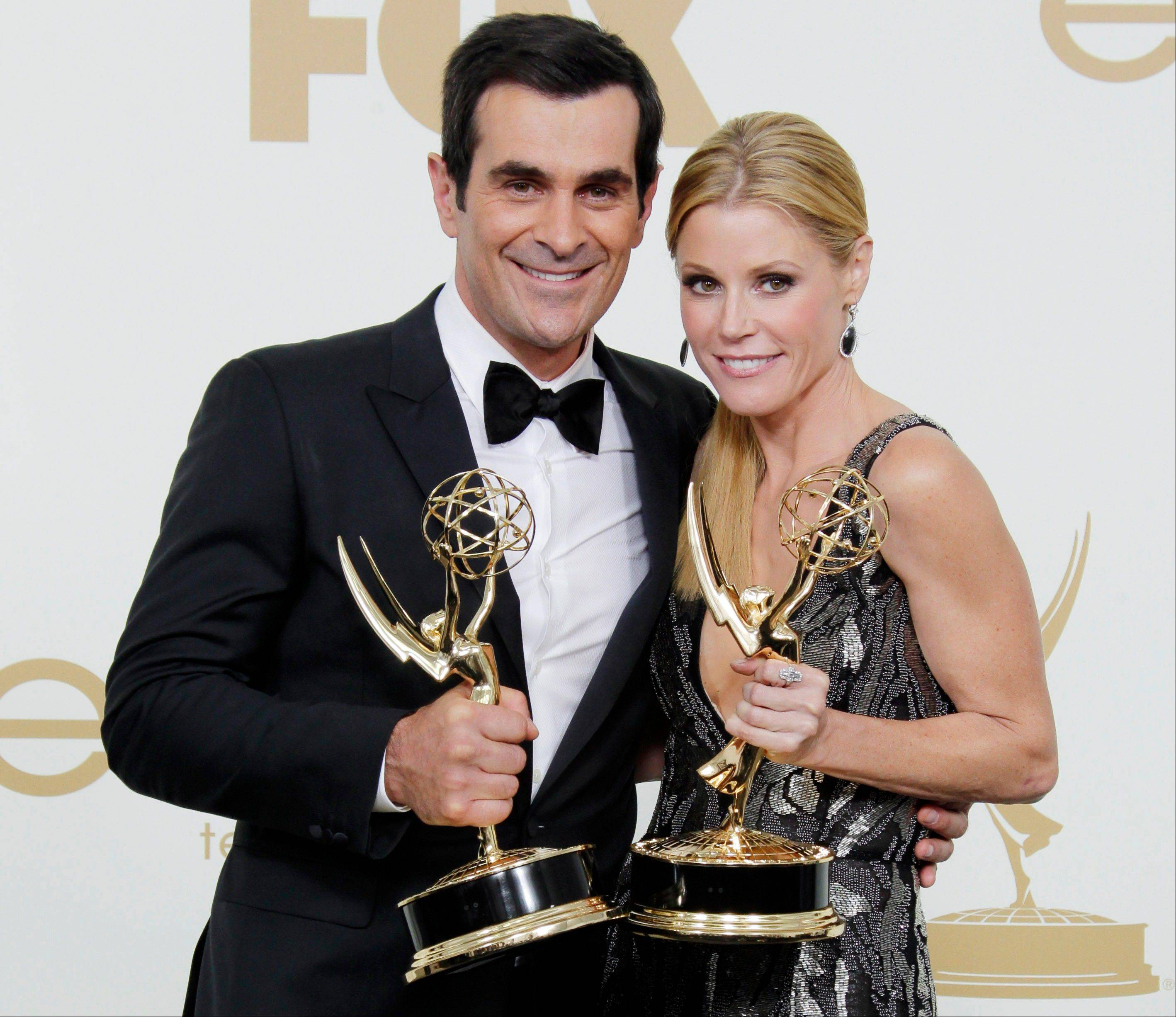 "This Sept. 18, 2011 file photo shows Ty Burrell, left, Julie Bowen from the television series ""Modern Family"" holding their Emmys for best supporting and actress actress in a comedy, backstage at the 63rd Primetime Emmy Awards in Los Angeles. Five stars of the hit ABC series sued 20th Century Fox Television on Tuesday July 24, 2012, claiming their contracts with the studio are illegal under California law and should be invalidated."