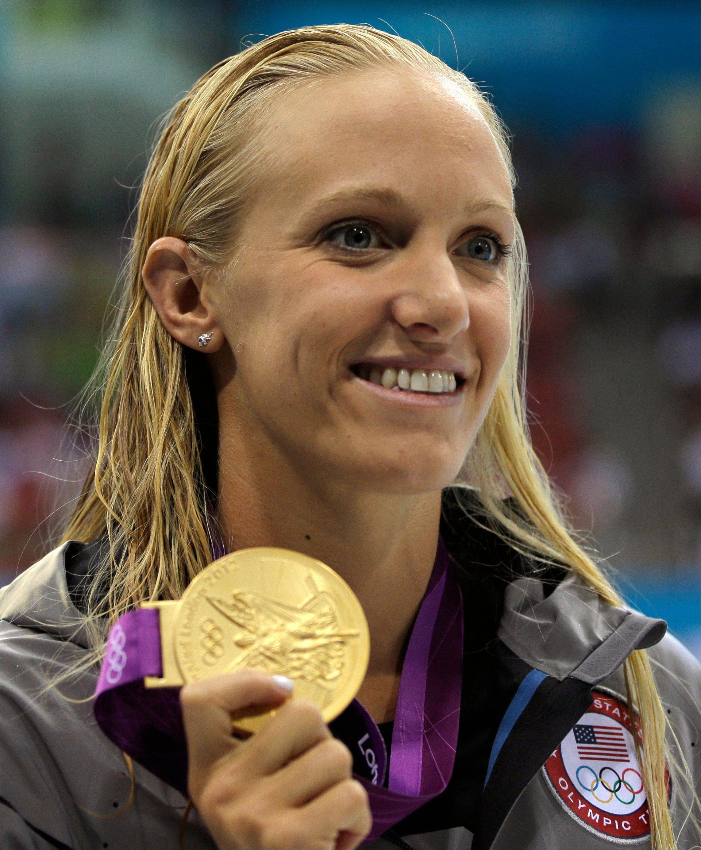 United States' Dana Vollmer holds her gold medal for her win in the women's 100-meter butterfly swimming final at the Aquatics Centre in the Olympic Park during the 2012 Summer Olympics in London. She set a world record in the win.