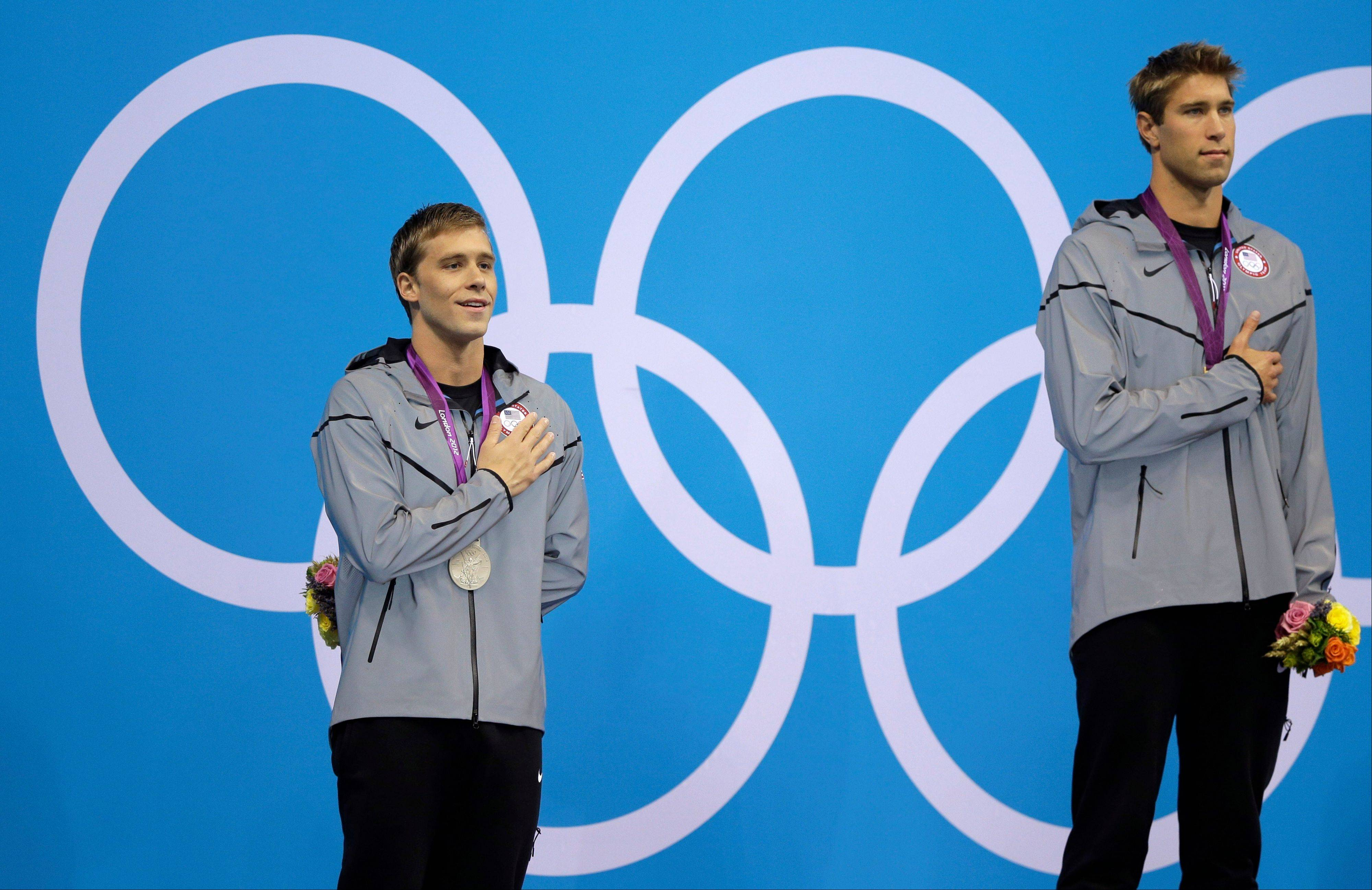 United States silver medalist Nick Thoman, left, and gold Matthew Grevers, right, listen to the U.S. national anthem during a ceremony following their wins in the men's 100-meter backstroke swimming final at the Aquatics Centre in the Olympic Park during the 2012 Summer Olympics in London, Monday, July 30, 2012.
