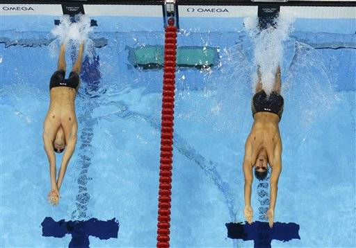 United States' Matthew Grevers, right, and France's Camille Lacourt start in the men's 100-meter backstroke swimming final at the Aquatics Centre in the Olympic Park during the 2012 Summer Olympics in London, Monday, July 30, 2012.