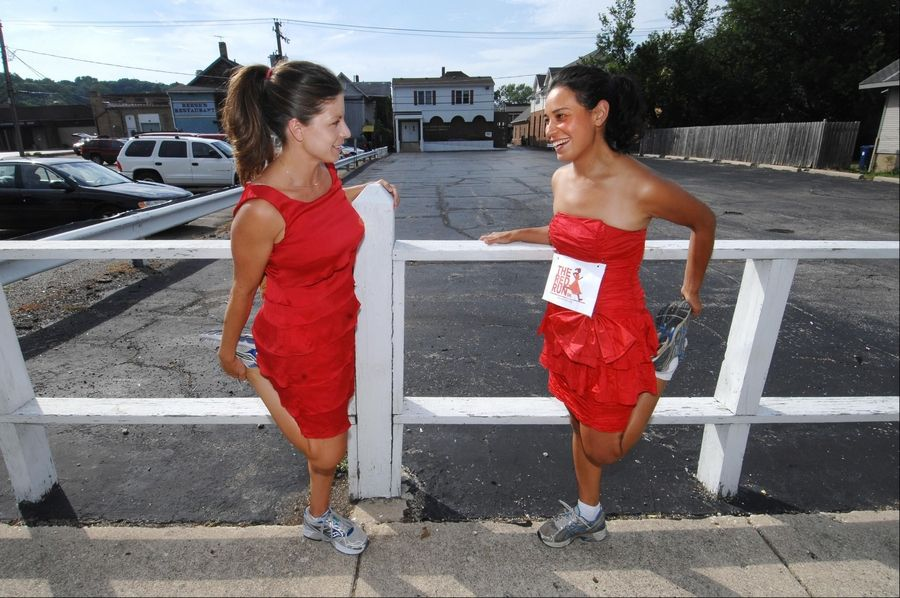 Kristen Guerrieri, left, and Cortina Nystad stretch before their regular run at rush hour in Algonquin. The dresses symbolize their fight against child sex trafficking. They have organized the Red Run 5K Run/Walk on Aug. 11 to benefit organizations who help combat the problem.